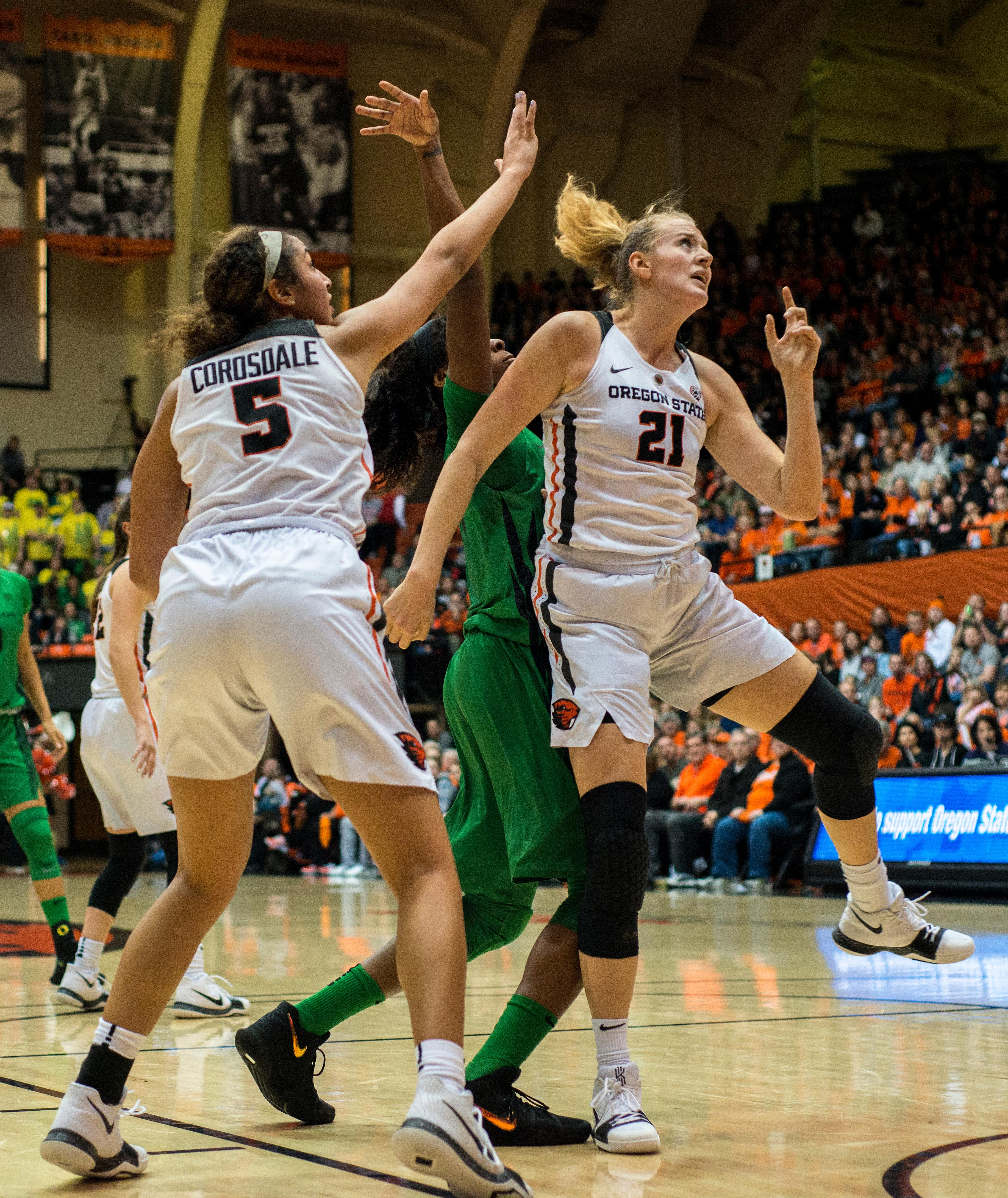 Oregon State Beavers forwards Marie Gülich (#21) and Taya Corosdale (#5) land from defending the Oregon Ducks offense.The Oregon Ducks were defeated by the Oregon State Beavers 85-79 on Friday night in Corvallis. Sabrina Ionescu scored 35 points and Ruthy Hebard added 24. The Ducks will face the Beavers this Sunday at 5 p.m. at Matthew Knight Arena. Photo by Abigail Winn, Oregon News Lab