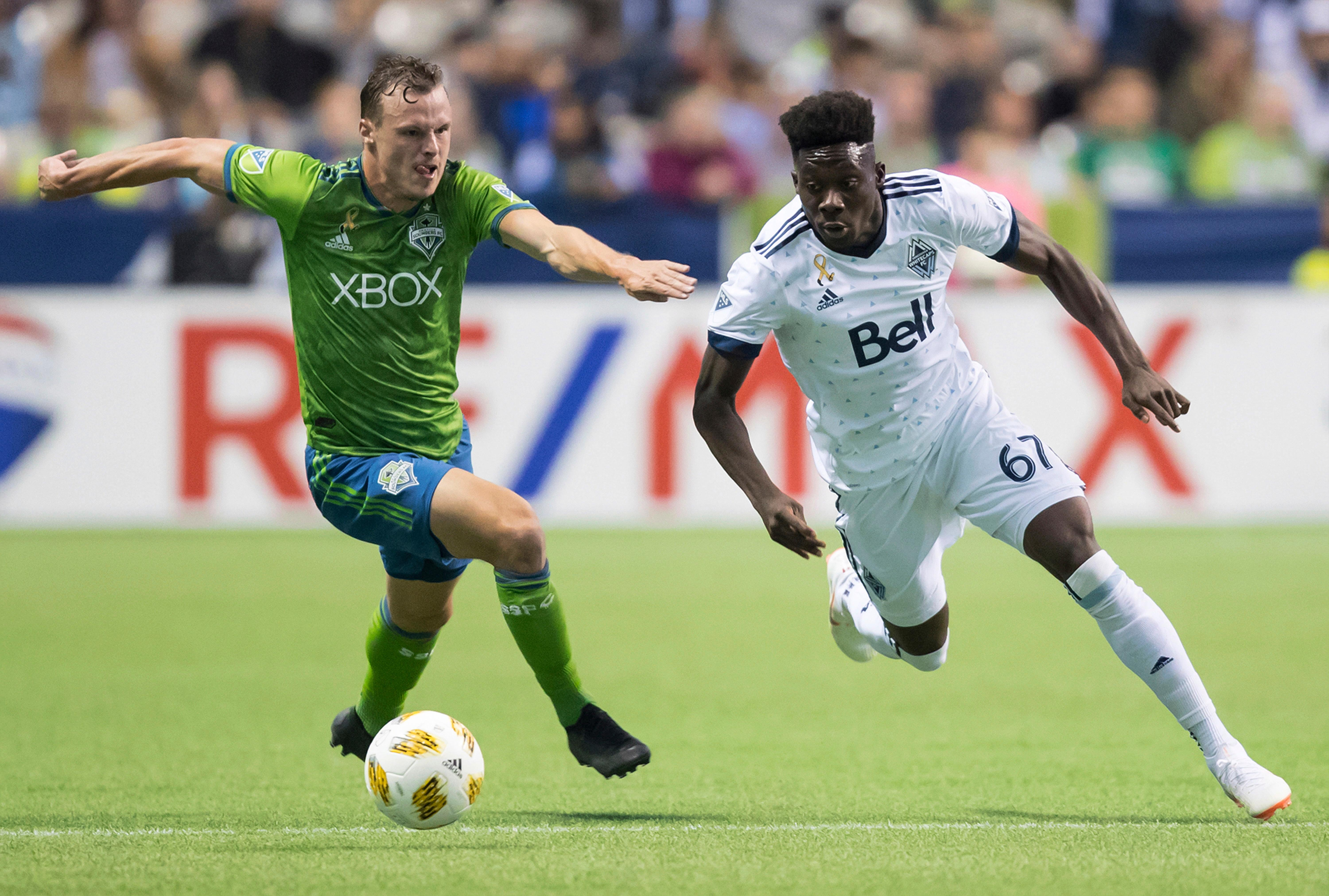 Vancouver Whitecaps' Alphonso Davies, right, runs past Seattle Sounders' Brad Smith with the ball during the first half of an MLS soccer match, Saturday, Sept. 15, 2018, in Vancouver, British Columbia. (Darryl Dyck/The Canadian Press via AP)