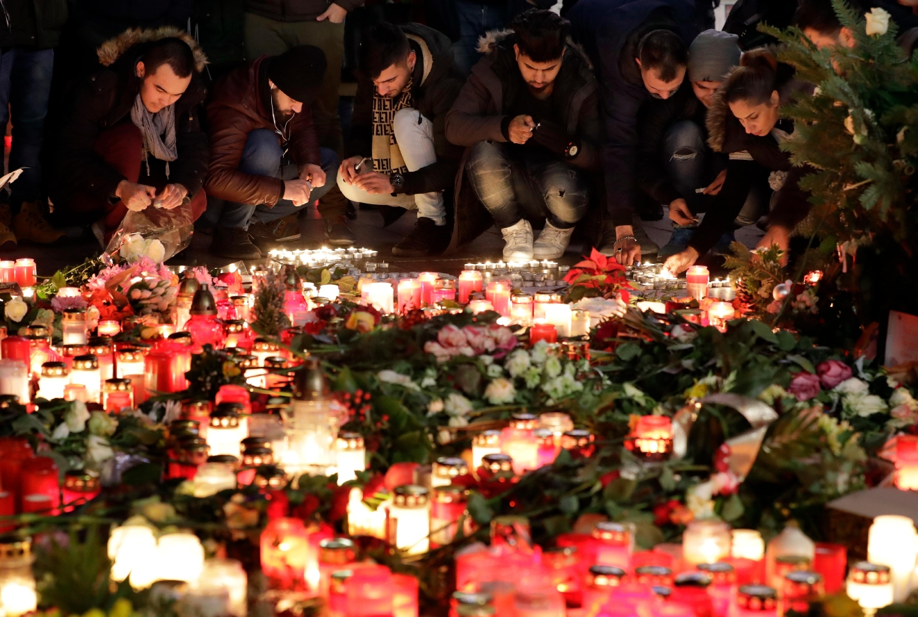 People light candles close to a Christmas market beside the memorial church in Berlin, Germany, Wednesday, Dec. 21, 2016, two days after a truck ran into a crowded Christmas market and killed several people. (AP Photo/Michael Sohn)