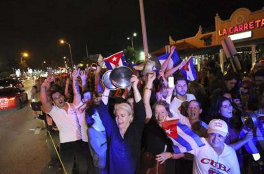 The Cuban community celebrates the announcement that Fidel Castro died in front La Carreta Restaurant, early Saturday, Nov. 26, 2016, in Miami. Within half an hour of the Cuban government's official announcement that former President Fidel Castro had died, Friday, Nov. 25, 2016, at age 90, Miami's Little Havana teemed with life - and cheers. (David Santiago/El Nuevo Herald via AP)