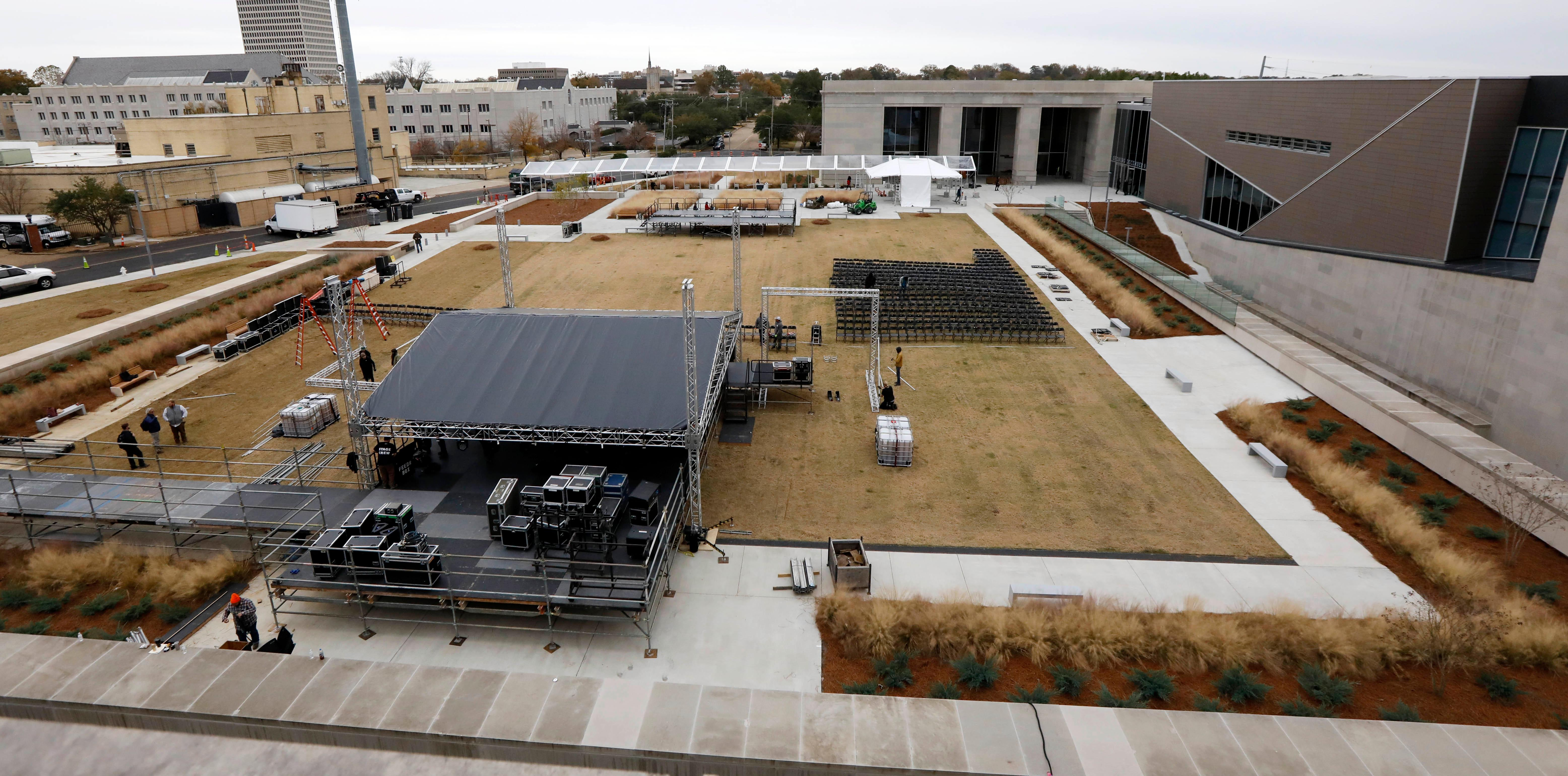 Work crews rush to set up a stage beside the state's two newest museums, the Museum of Mississippi History and the Mississippi Civil Rights Museum, Thursday, Dec. 7, 2017 in Jackson, Miss. The long-planned Saturday ceremony will mark Mississippi's bicentennial of admission into the union, however the appearance of President Donald Trump at the ceremony has drawn the ire of U.S. Reps. John Lewis, D-Ga., and Bennie Thompson, D-Miss., who announced Thursday they won't attend the opening of Mississippi civil rights and history museums. What was intended as a moment of racial unity and atonement in the state with the largest share of African-Americans is descending into racial and partisan strife after Republican Mississippi Gov. Phil Bryant invited fellow Republican Trump to attend. (AP Photo/Rogelio V. Solis)