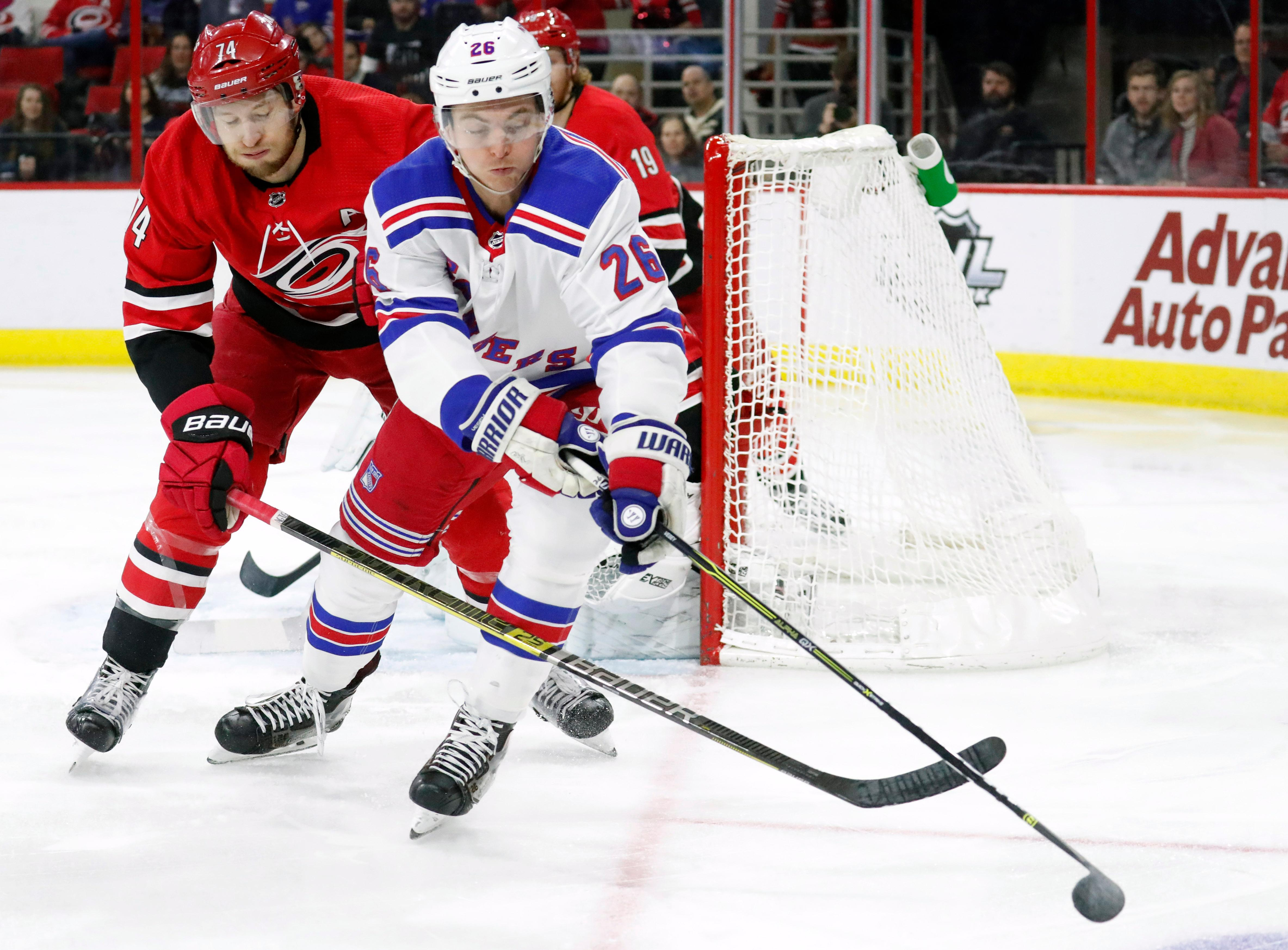 Carolina Hurricanes' Jaccob Slavin, left, and New York Rangers' Jimmy Vesey, right,  vie for the puck during the first period of an NHL hockey game in Raleigh, N.C., Tuesday, Feb. 19, 2019. (AP Photo/Chris Seward)