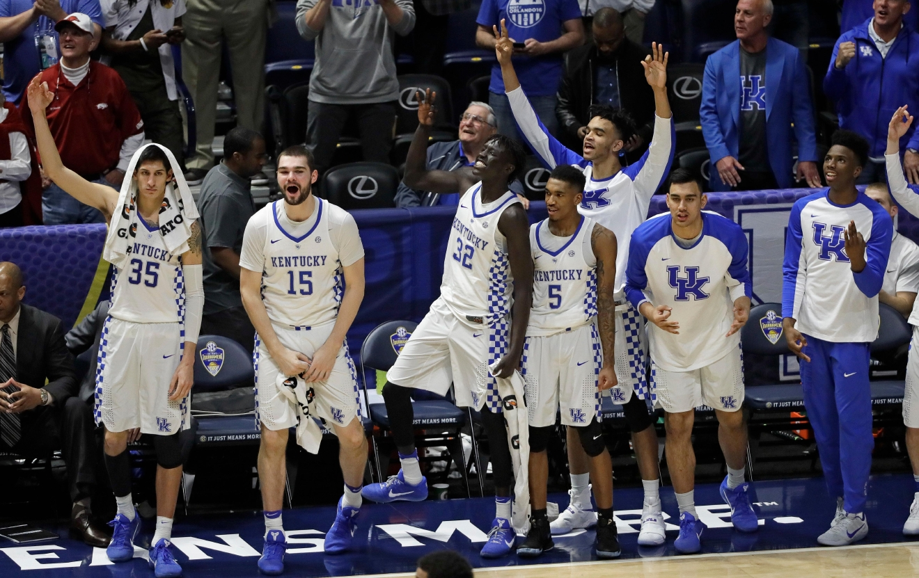 Kentucky players celebrate in the final seconds of an NCAA college basketball game against Arkansas for the championship of the Southeastern Conference tournament Sunday, March 12, 2017, in Nashville, Tenn. Kentucky won 82-65. (AP Photo/Mark Humphrey)