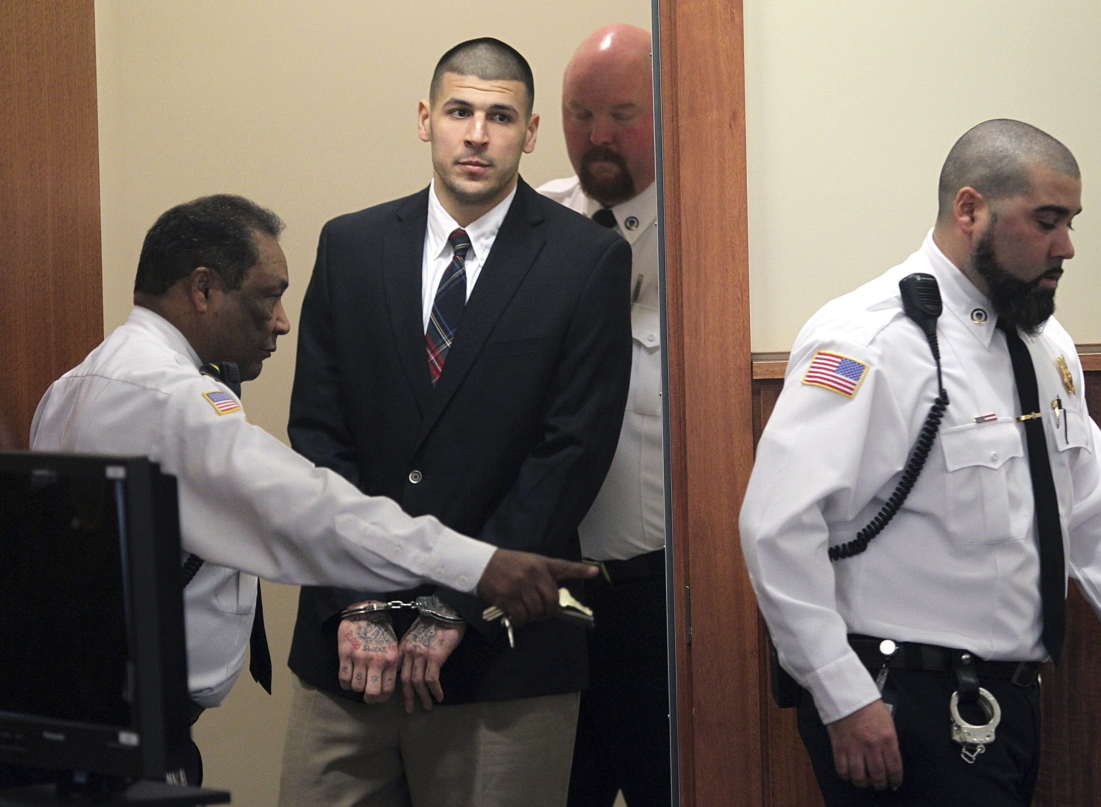 FILE - In this Monday, Dec. 23, 2013, file photo, former New England Patriots NFL football player Aaron Hernandez is led into his court appearance at the Fall River Superior Court in Fall River, Mass. Massachusetts prison officials said Hernandez hanged himself in his cell and was pronounced dead at a hospital early Wednesday, April 19, 2017. (Matt Stone/The Boston Herald via AP, Pool, File)