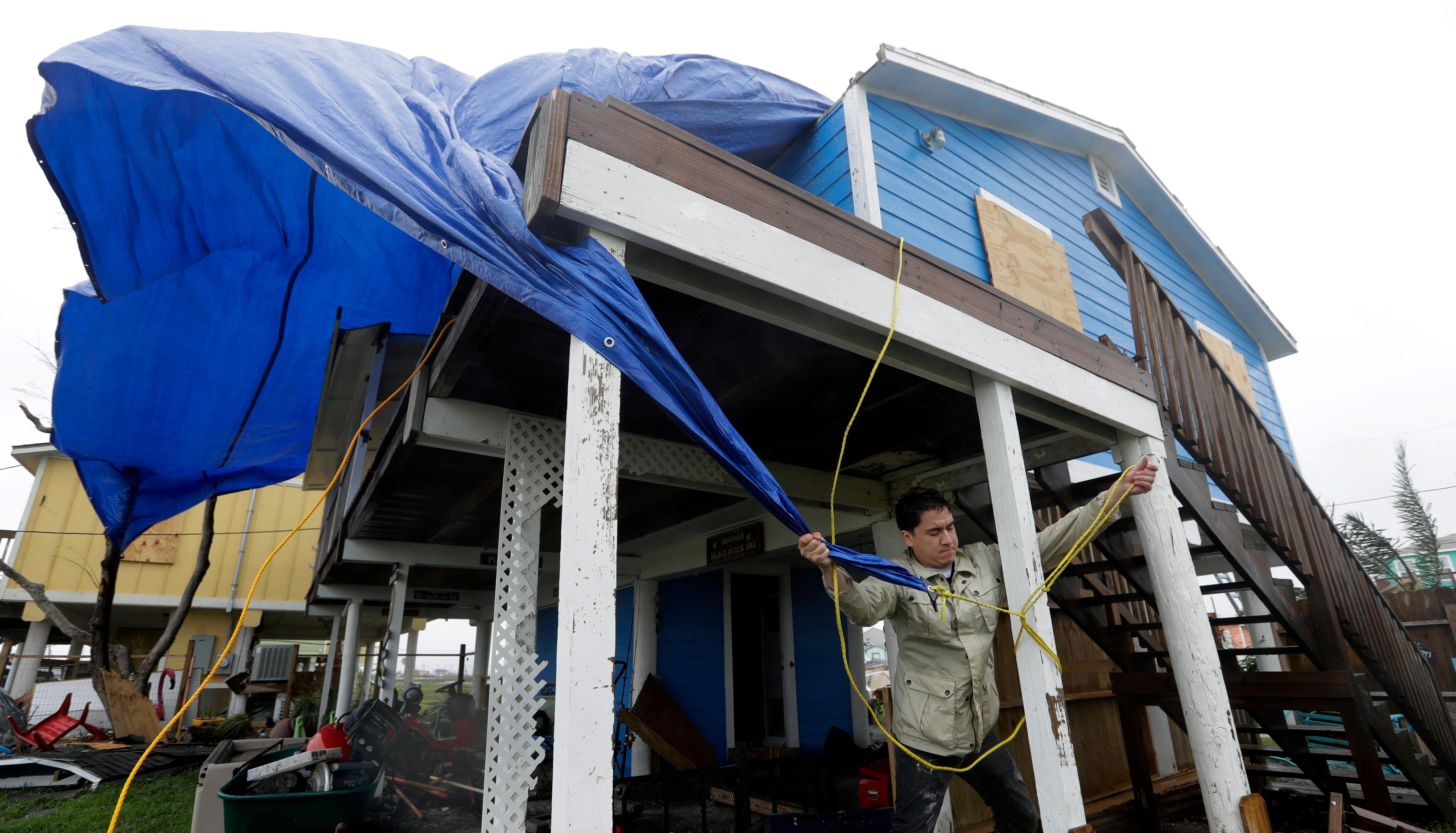 Shawn Hagdorn helps to cover the roof of his father's home that was damaged in the wake of Hurricane Harvey, Monday, Aug. 28, 2017, in Rockport, Texas. (AP Photo/Eric Gay)