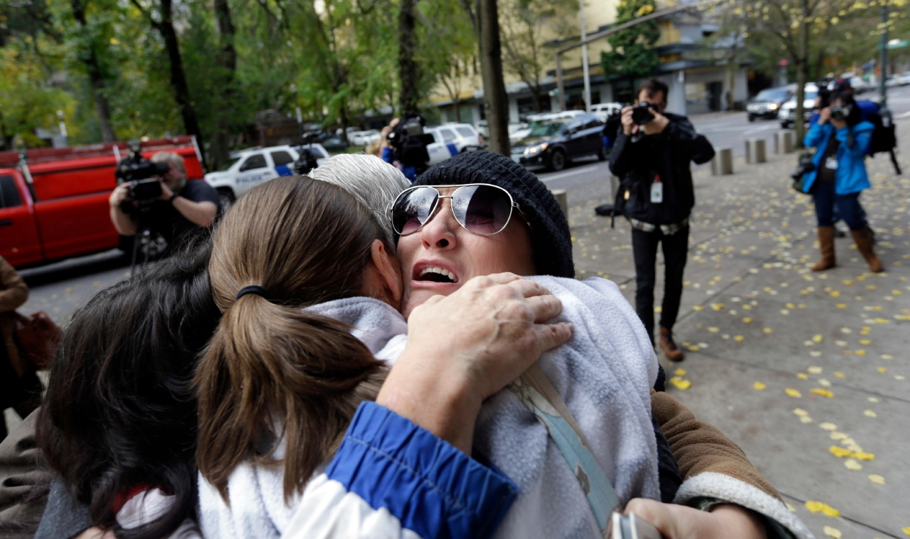 Supporters hug and cry after hearing a verdict outside federal court in Portland, Ore., Thursday, Oct. 27, 2016. A jury exonerated brothers Ammon and Ryan Bundy and five others of conspiring to impede federal workers from their jobs at the Malheur National Wildlife Refuge. (AP Photo/Don Ryan)
