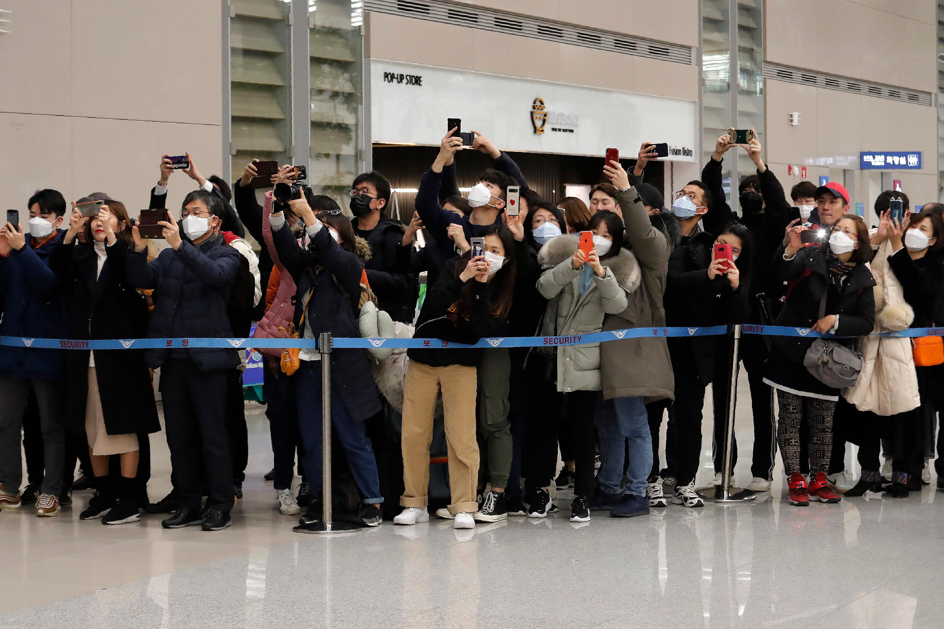 "People take photos of South Korean director Bong Joon-ho upon his arrival at the Incheon International Airport in Incheon, South Korea, Sunday, Feb. 16, 2020. South Koreans are reveling in writer-director Bong's dark comic thriller, ""Parasite,"" which won this year's Academy Awards for best film and best international feature. The movie itself, however, doesn't put the country in a particularly positive light. (AP Photo/Ahn Young-joon)"