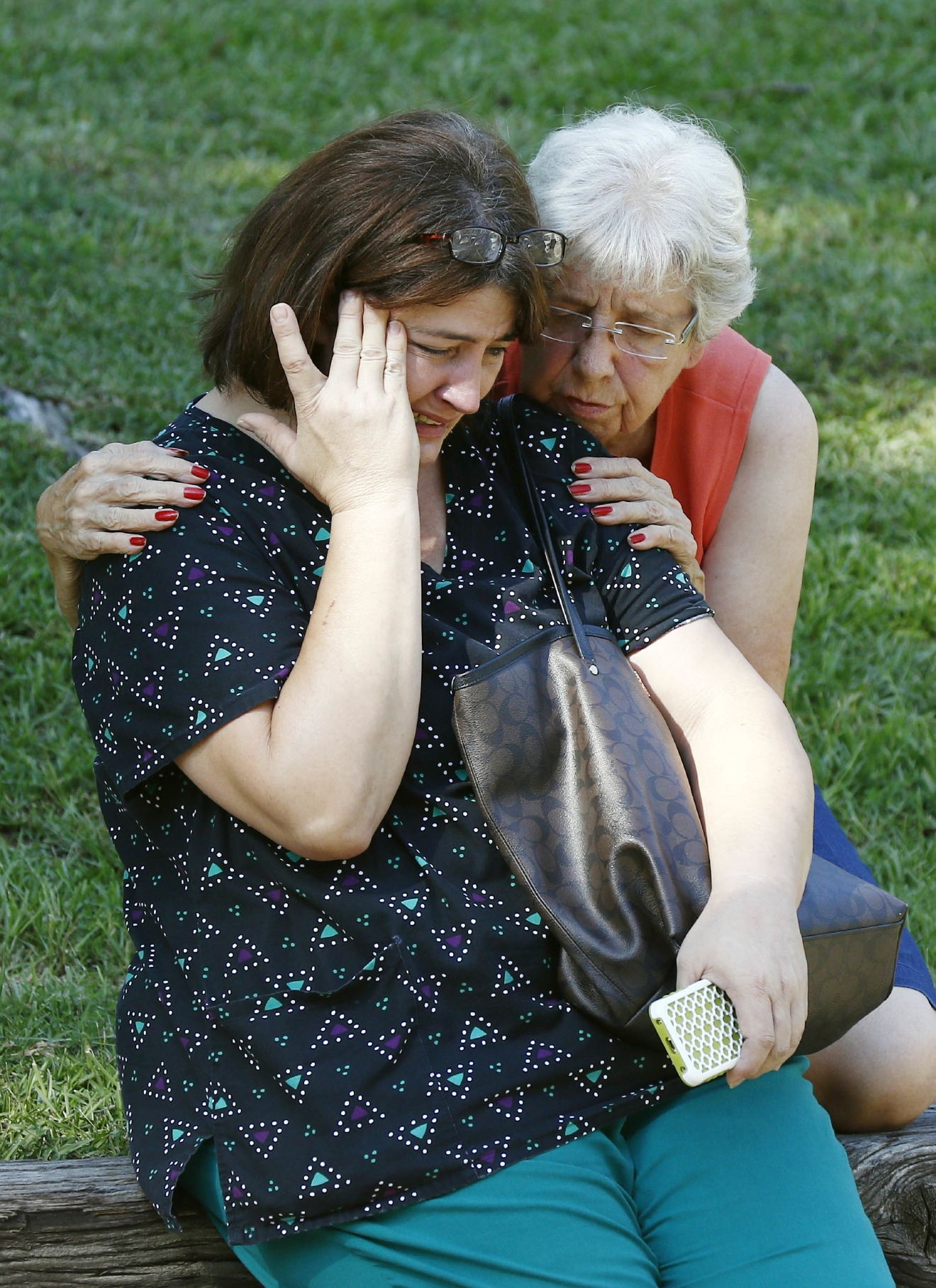 Jonell Payton, right, comforts Lisa Dew, outside the Durant, Miss., home of two slain Catholic nuns, Thursday, Aug. 25, 2016.  (AP Photo/Rogelio V. Solis)