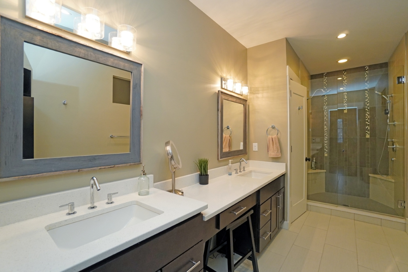 The master bath has a double vanity with quartz countertops and a generously-sized shower. The second full bathroom has a large tub surrounded by subway tile. / Image courtesy of Brian Hubert via Comey & Shepherd{ }Realtors  // Published: 6.9.20