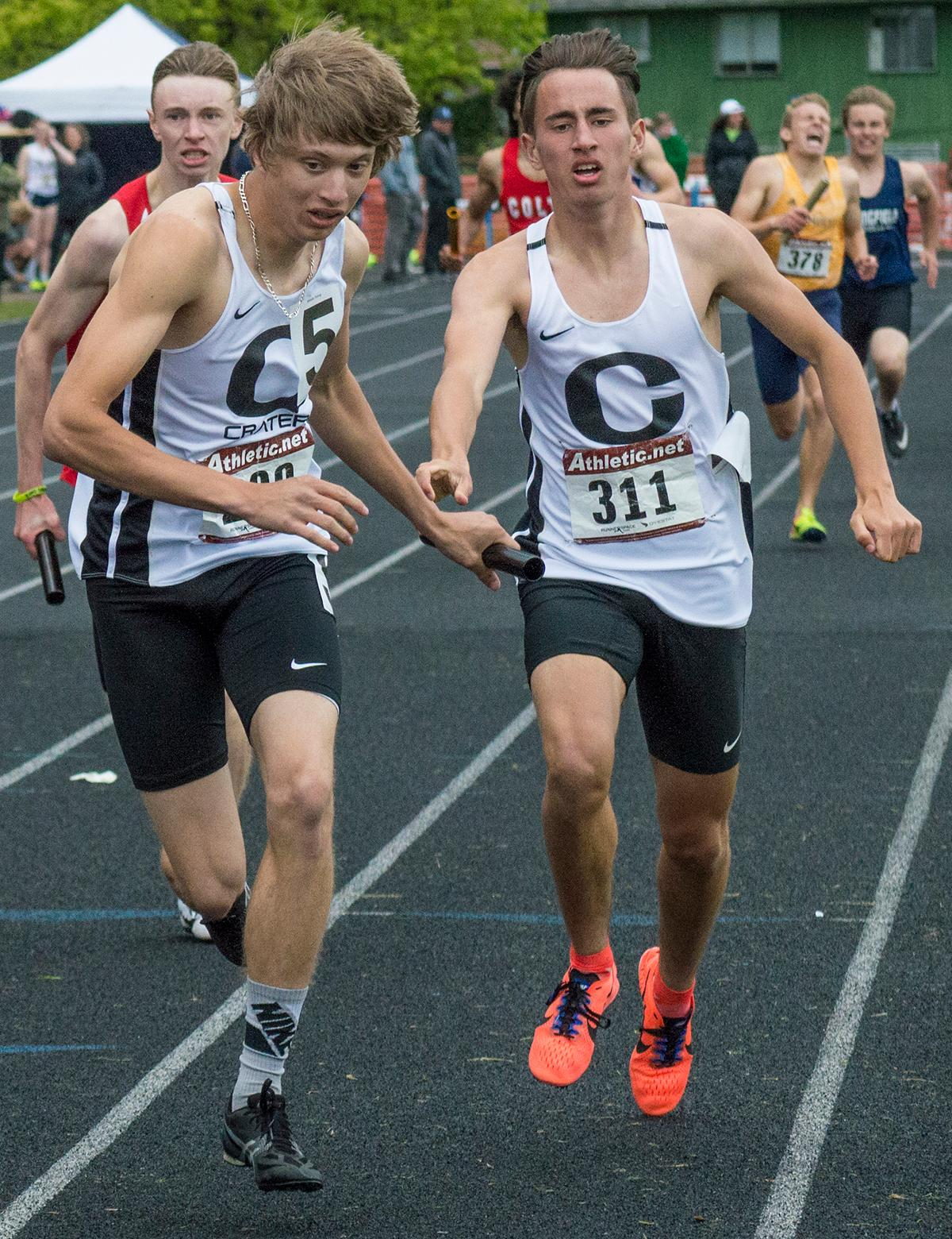 Crater High School's Ryland McCullough passes the baton to anchor Cal Duke in the Men's 4 x 400m event. The Comets took first place in the event at the 5A-3 Midwestern League District Championship with a time of 3:28.91. Photo by Emily Gonzalez, Oregon News Lab.