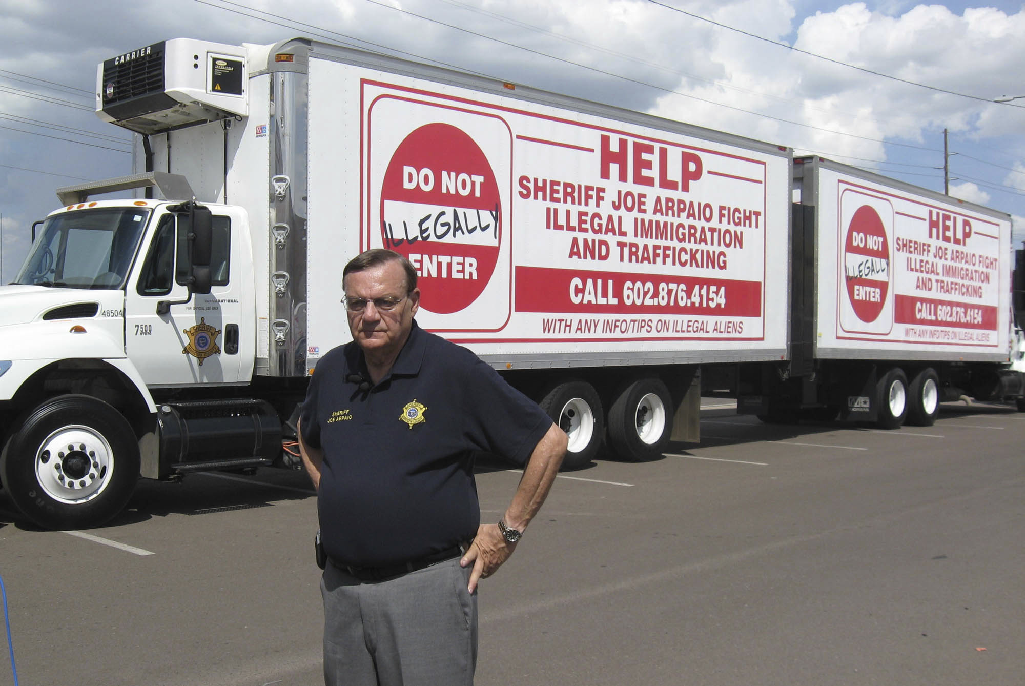 FILE--In this Sept. 16, 2007, file photo, Maricopa County Sheriff Joe Arpaio shows off vehicles advertising a hotline to report undocumented immigrants in Phoenix, Ariz. Arpaio has been convicted of a criminal charge Monday, July 31, 2017, for disobeying a court order to stop traffic patrols that targeted immigrants in a conviction that marks a final rebuke for the former sheriff and politician who once drew strong popularity from such crackdowns but was booted from office amid voter frustrations over his deepening legal troubles. (Larry Fehr-Snyder/Arizona Republic via AP, file)