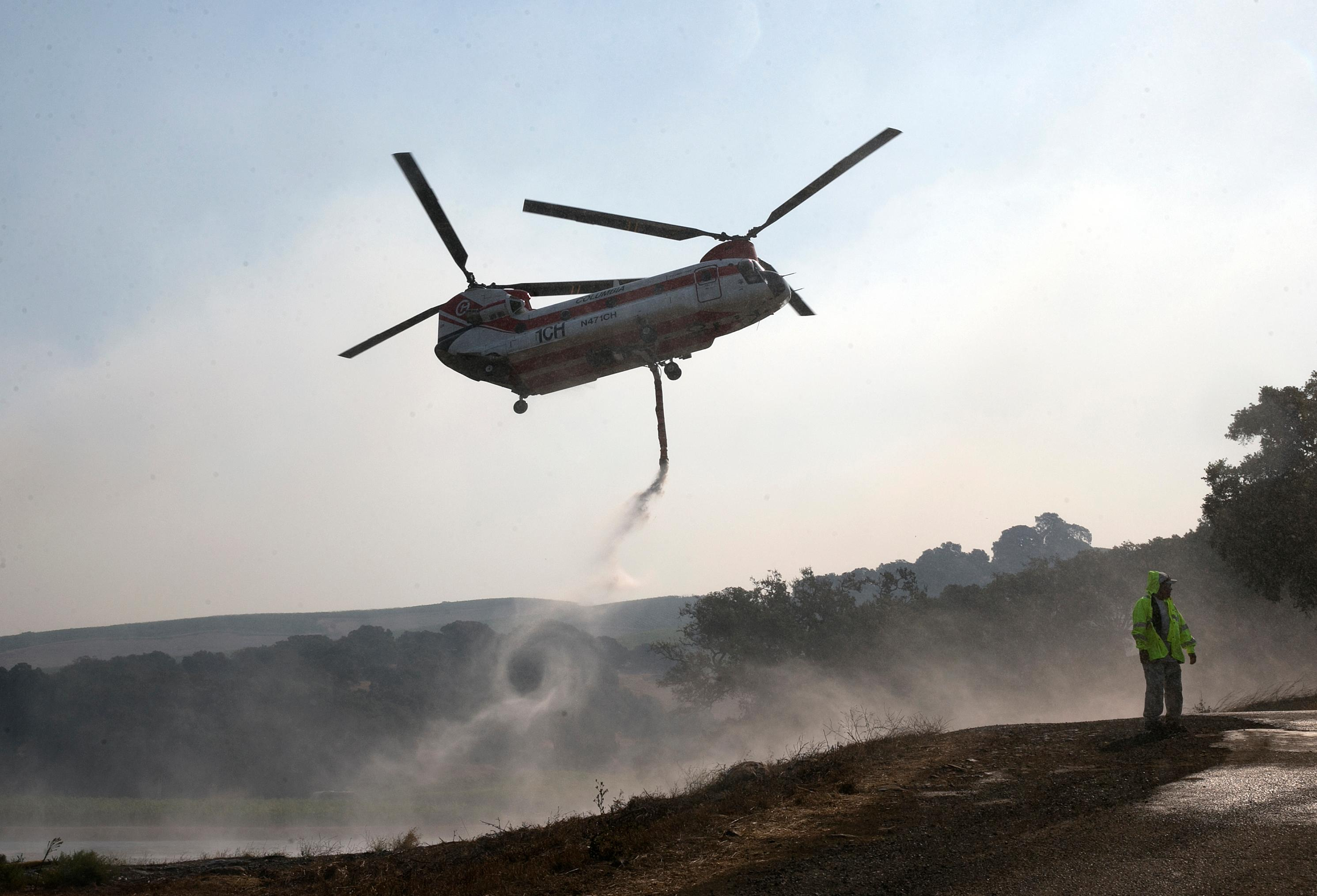 A helicopter draws water from a pond to help put out a fire near Napa, Calif., on Thursday, Oct. 12, 2017.  Gusting winds and dry air forecast for Thursday could drive the next wave of devastating wildfires.  (AP Photo/Rich Pedroncelli)