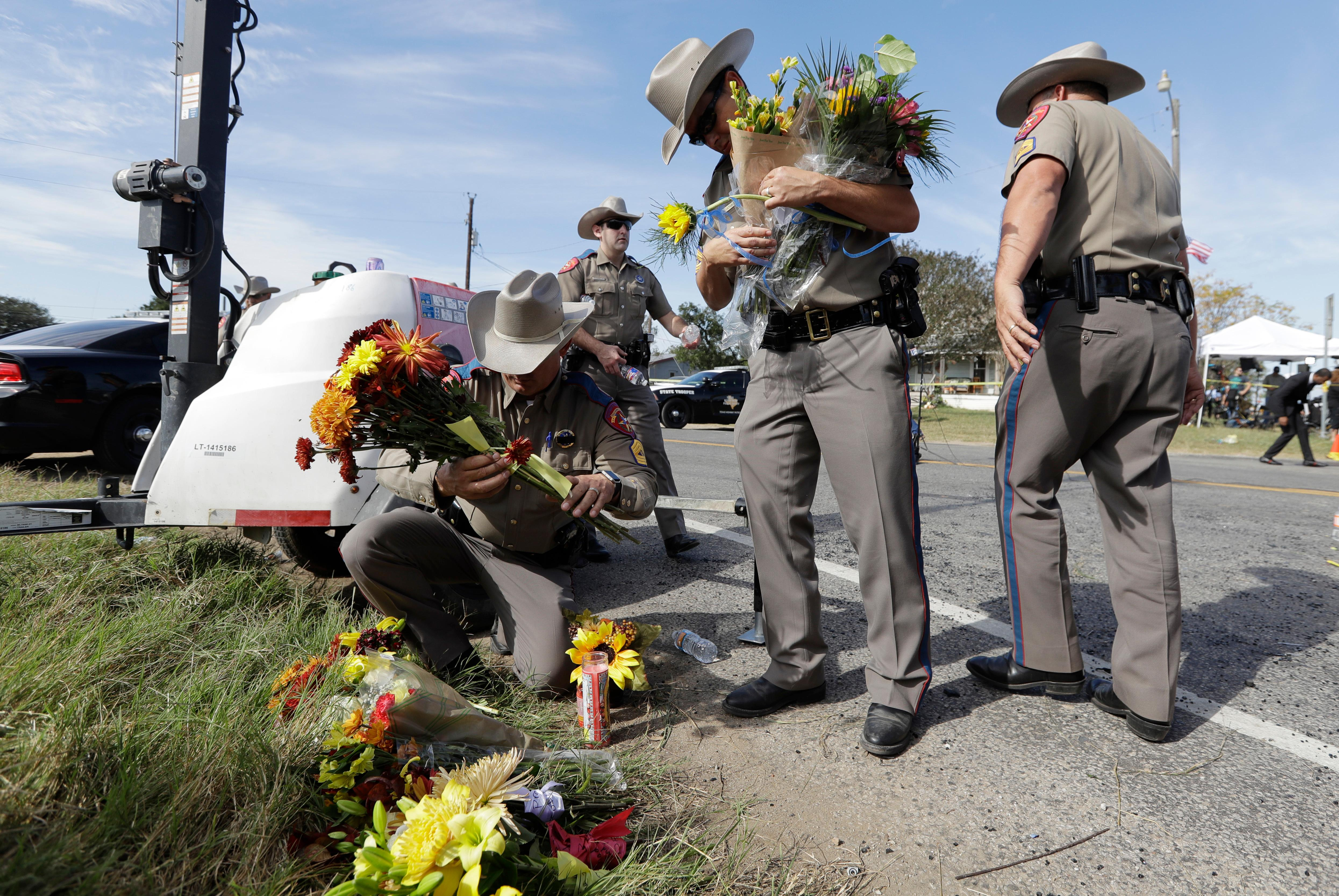 Law enforcement officials move flowers left at the scene of a shooting at the First Baptist Church of Sutherland Springs, Monday, Nov. 6, 2017, in Sutherland Springs, Texas. A man opened fire inside the church in the small South Texas community on Sunday, killing and wounding many. (AP Photo/Eric Gay)