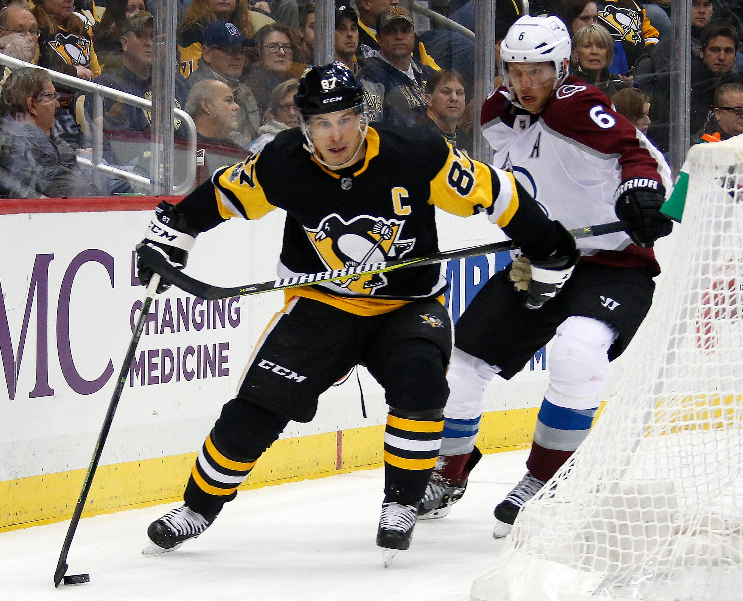 Pittsburgh Penguins' Sidney Crosby (87) works the puck behind the net with Colorado Avalanche's Erik Johnson (6) defending in the second period of an NHL hockey game in Pittsburgh, Monday, Dec. 11, 2017. (AP Photo/Gene J. Puskar)