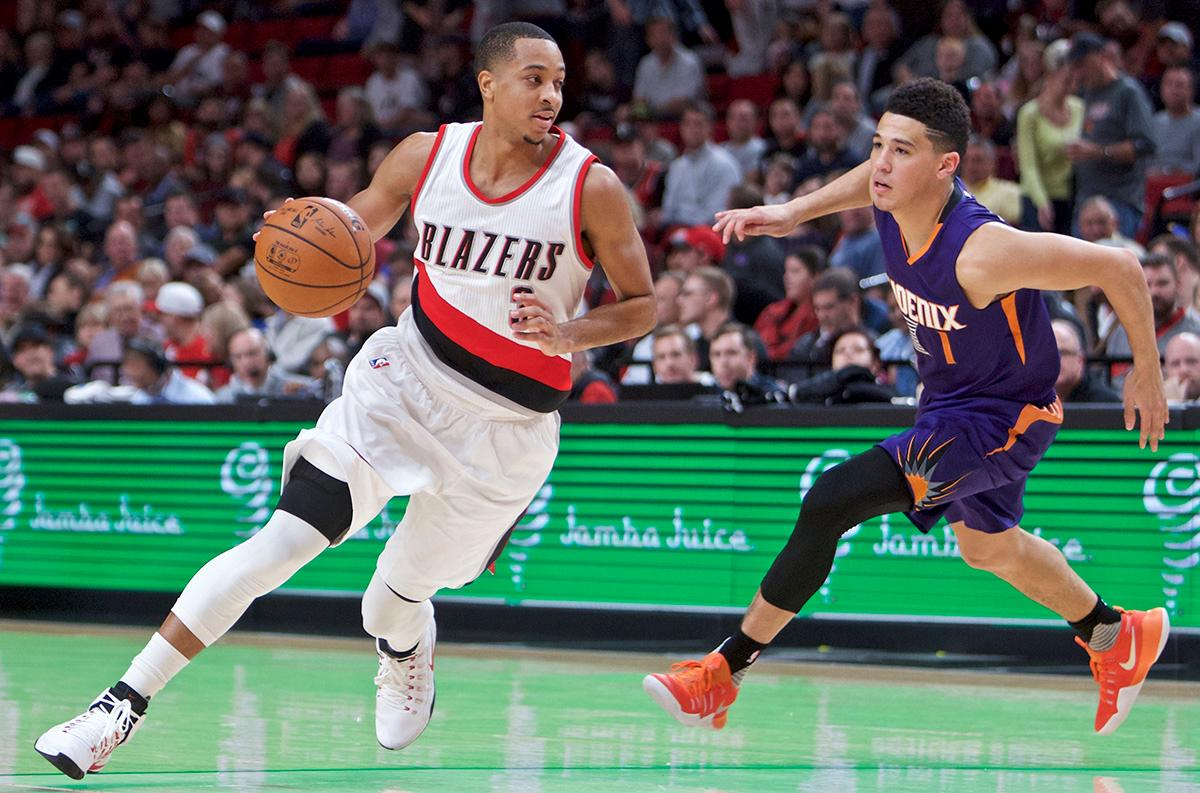 Portland Trail Blazers guard C.J. McCollum, left, dribbles past Phoenix Suns guard Devin Booker during the first half of an NBA basketball game in Portland, Ore., Tuesday, Nov. 8, 2016. (AP Photo/Craig Mitchelldyer)