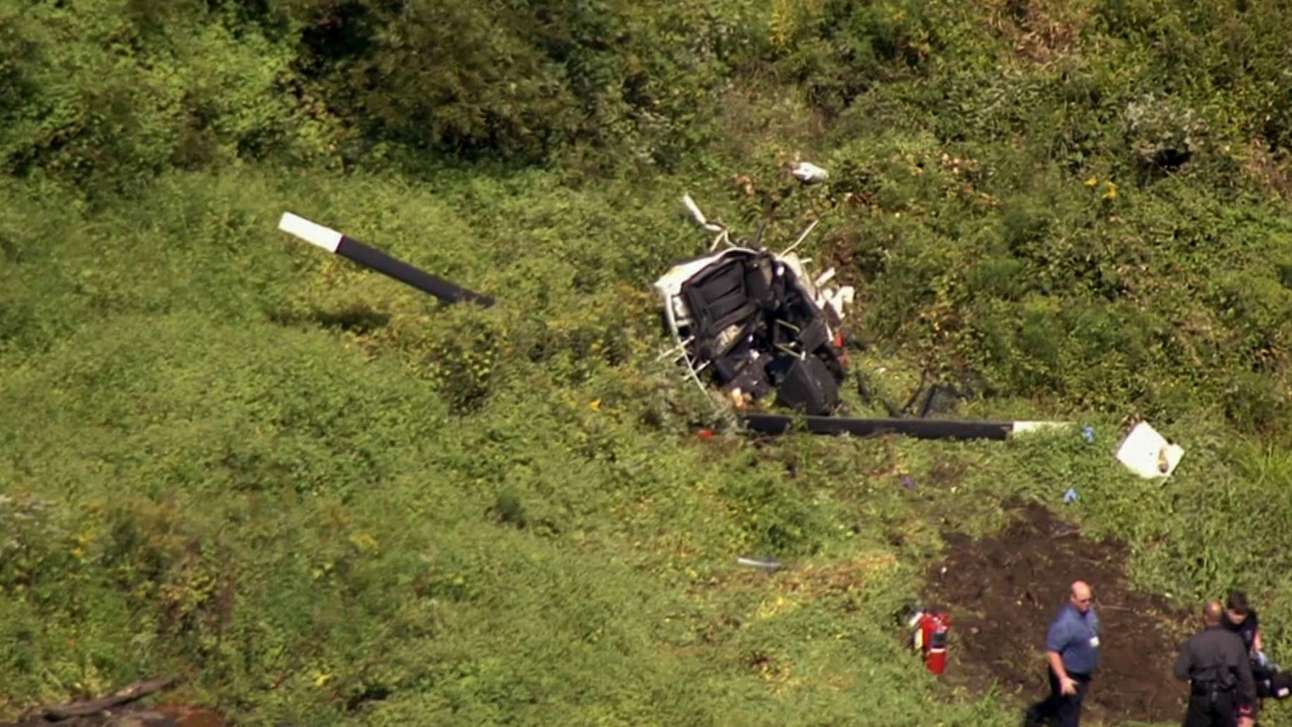 In this image from video provided by NBC10 Philadelphia, first responders are positioned near the wreckage of a helicopter in Lumberton, N.J., Friday, Sept. 8, 2017. The Federal Aviation Administration says the helicopter crashed into a wooded area near the Flying W Airport in Medford, N.J., about 20 miles east of Philadelphia. The official website for Montgomery Gentry says Troy Gentry, half of the country duo, died in the crash.  (NBC10 Philadelphia via AP)