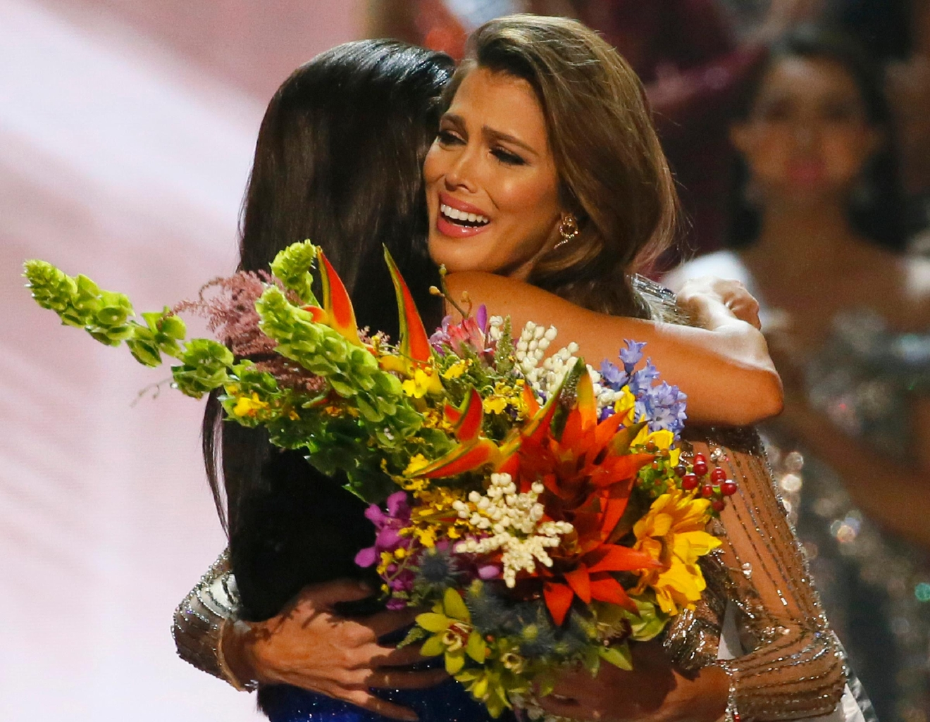 Miss Universe 2016 Iris Mittenaere, right, of France is hugged by Miss Universe 2015 Pia Wurtzbach following coronation Monday, Jan. 30, 2017, at the Mall of Asia in suburban Pasay city, south of Manila, Philippines. (AP Photo/Bullit Marquez)