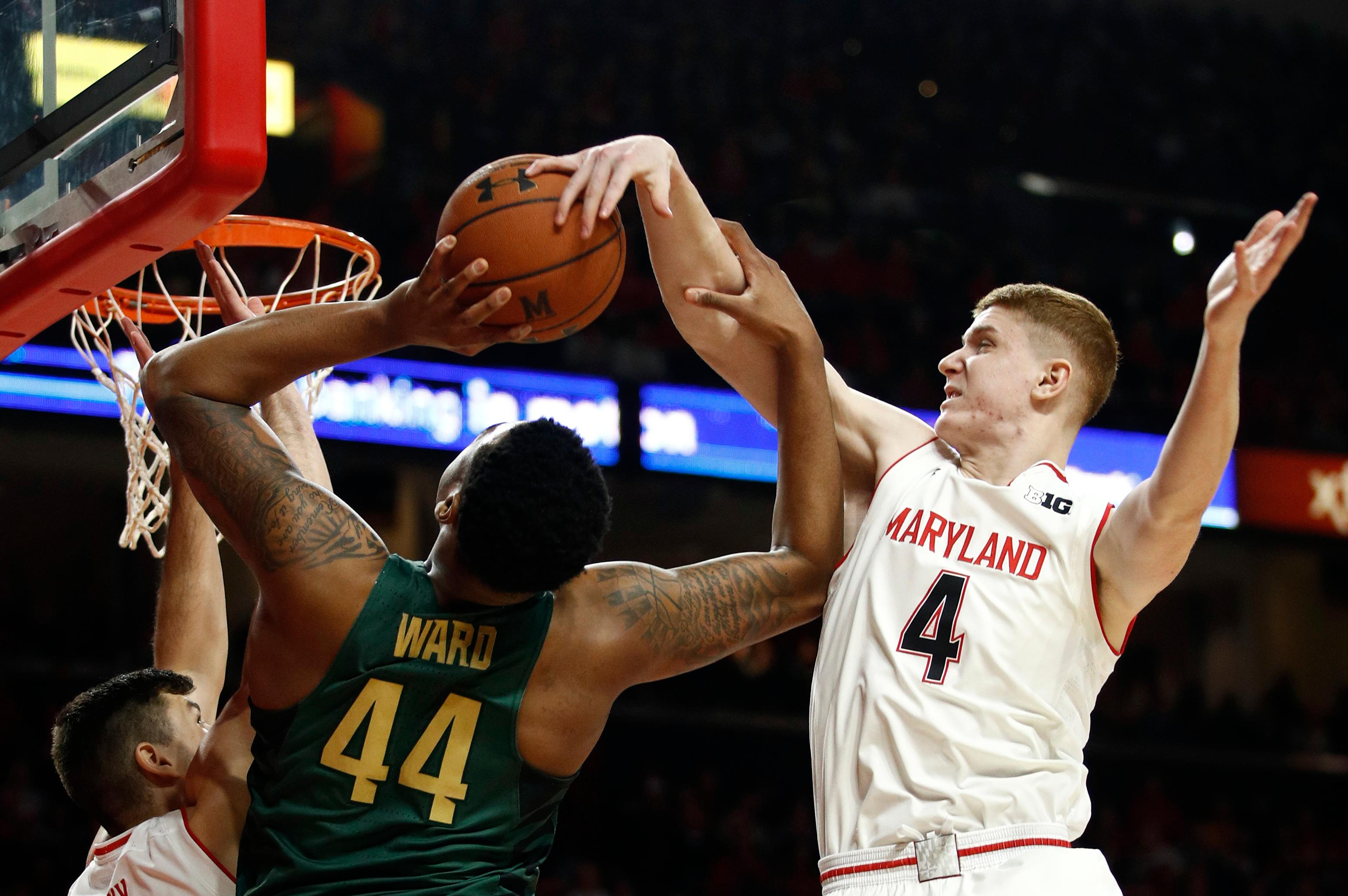 Maryland guard Kevin Huerter, right, tries to block a shot-attempt by Michigan State forward Nick Ward in the first half of an NCAA college basketball game in College Park, Md., Sunday, Jan. 28, 2018. (AP Photo/Patrick Semansky)