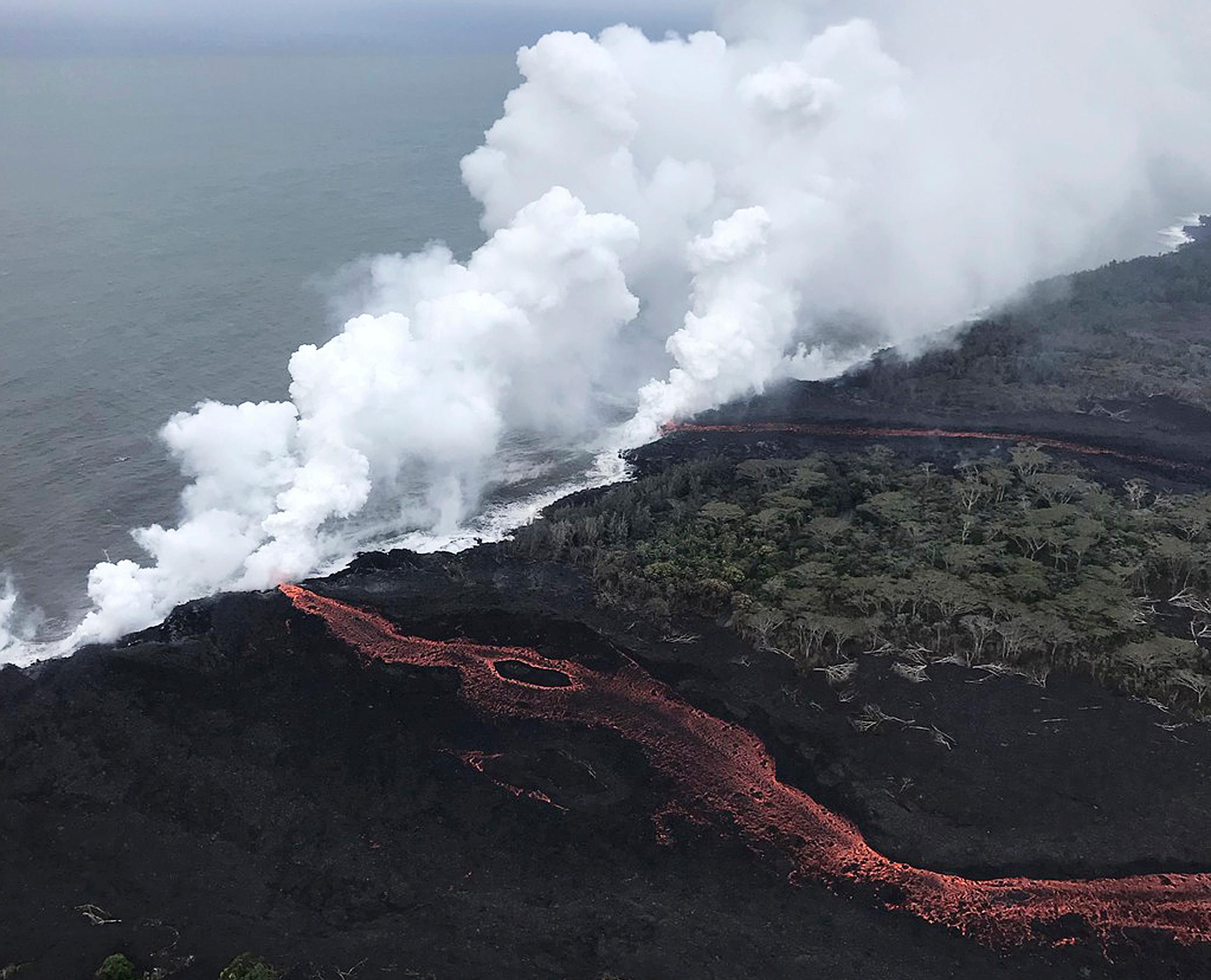 This image provided by the U.S. Geological Survey shows lava{ }as it continues to enter the sea at two locations near Pahoa, Hawaii, Monday, May 21, 2018. Lava from Hawaii's Kilauea volcano is pouring into the sea and setting off a chemical reaction that creates giant clouds of acid and fine glass. (U.S. Geological Survey via AP)