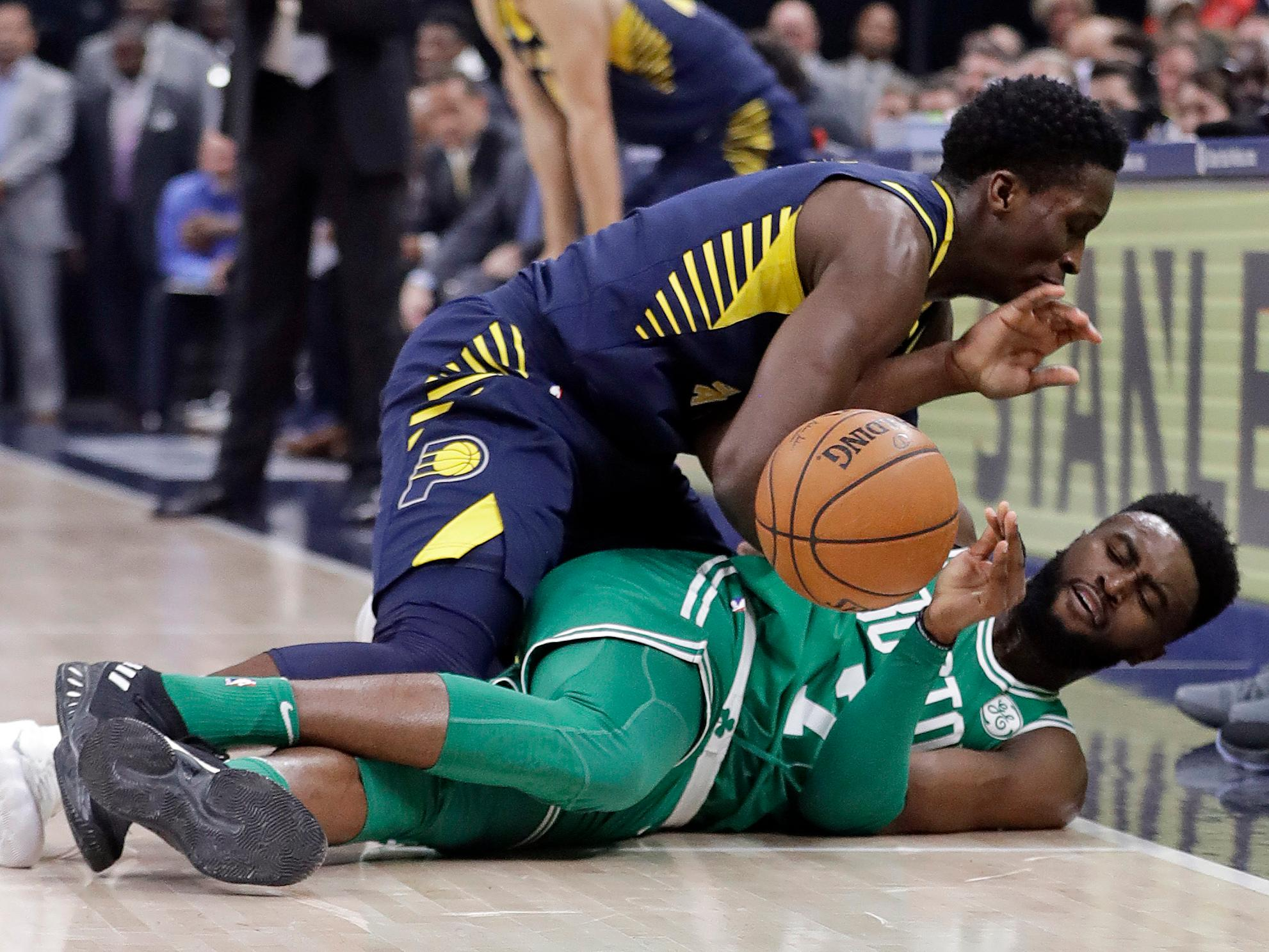 Indiana Pacers' Victor Oladipo, top, and Boston Celtics' Jaylen Brown battle for a loose ball during the first half of an NBA basketball game, Monday, Dec. 18, 2017, in Indianapolis.(AP Photo/Darron Cummings)