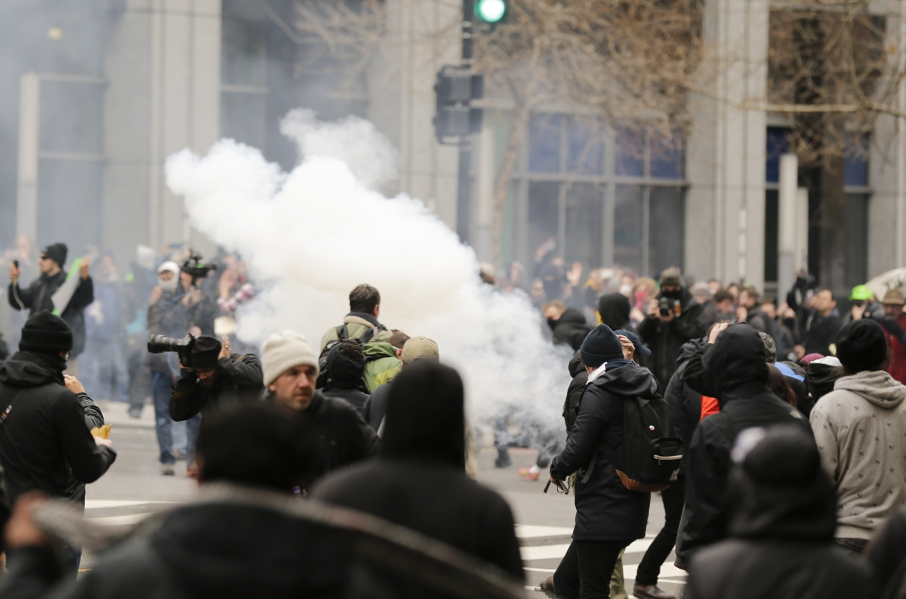 Police deploy smoke and pepper grenades during clashes with protesters in northwest Washington, Friday, Jan. 20, 2017. (AP Photo/Mark Tenally)