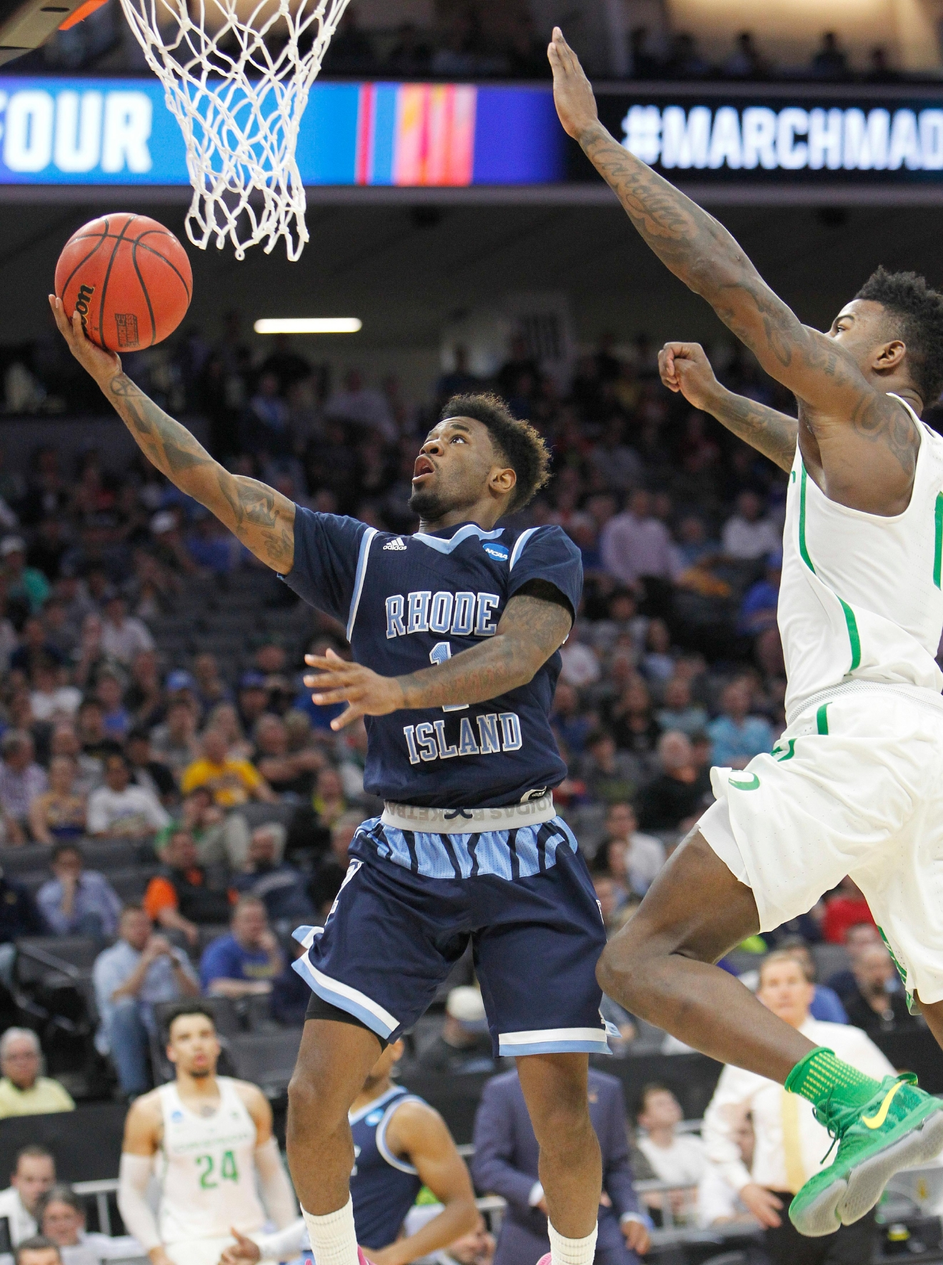 Rhode Island guard Jarvis Garrett, left, goes to the basket against Oregon forward Jordan Bell during the first half of a second-round game of the NCAA men's college basketball tournament in Sacramento, Calif., Sunday, March 19, 2017. (AP Photo/Steve Yeater)