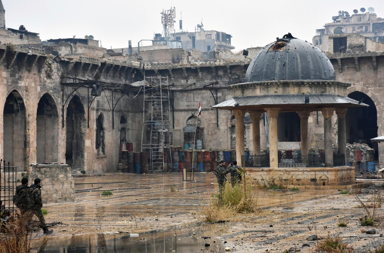 This photo released by the Syrian official news agency SANA, shows Syrian troops and pro-government gunmen marching walk inside the destroyed Grand Umayyad mosque in the old city of Aleppo, Syria, Tuesday, Dec. 13, 2016. Government forces and rebel fighters have fought to control the 12th century mosque in the last four years, until Syrian troops seized control of it this week. Syrian rebels said Tuesday that they reached a cease-fire deal with Moscow to evacuate civilians and fighters from eastern Aleppo, after the U.N. and opposition activists reported possible mass killings by government forces closing in on the rebels' last enclave.  (SANA via AP)
