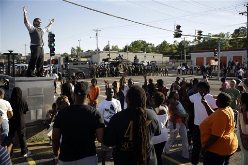 A man tries to calm a group of protesters as police stand in the distance in Ferguson, Mo.