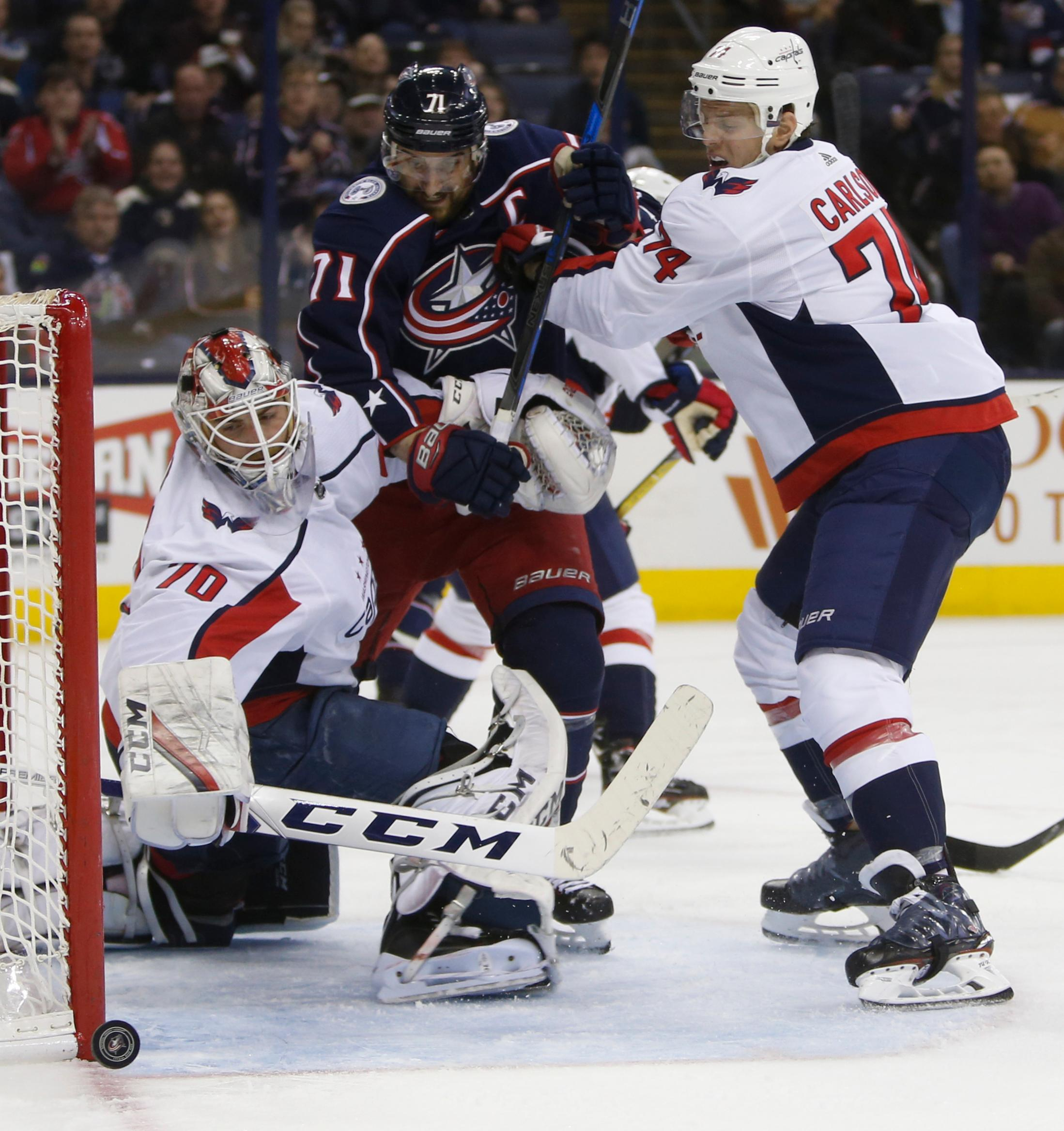 Washington Capitals' Braden Holtby, left, makes a save as teammate John Carlson, right, and Columbus Blue Jackets' Nick Foligno fight for position during the second period of an NHL hockey game Tuesday, Feb. 6, 2018, in Columbus, Ohio. (AP Photo/Jay LaPrete)