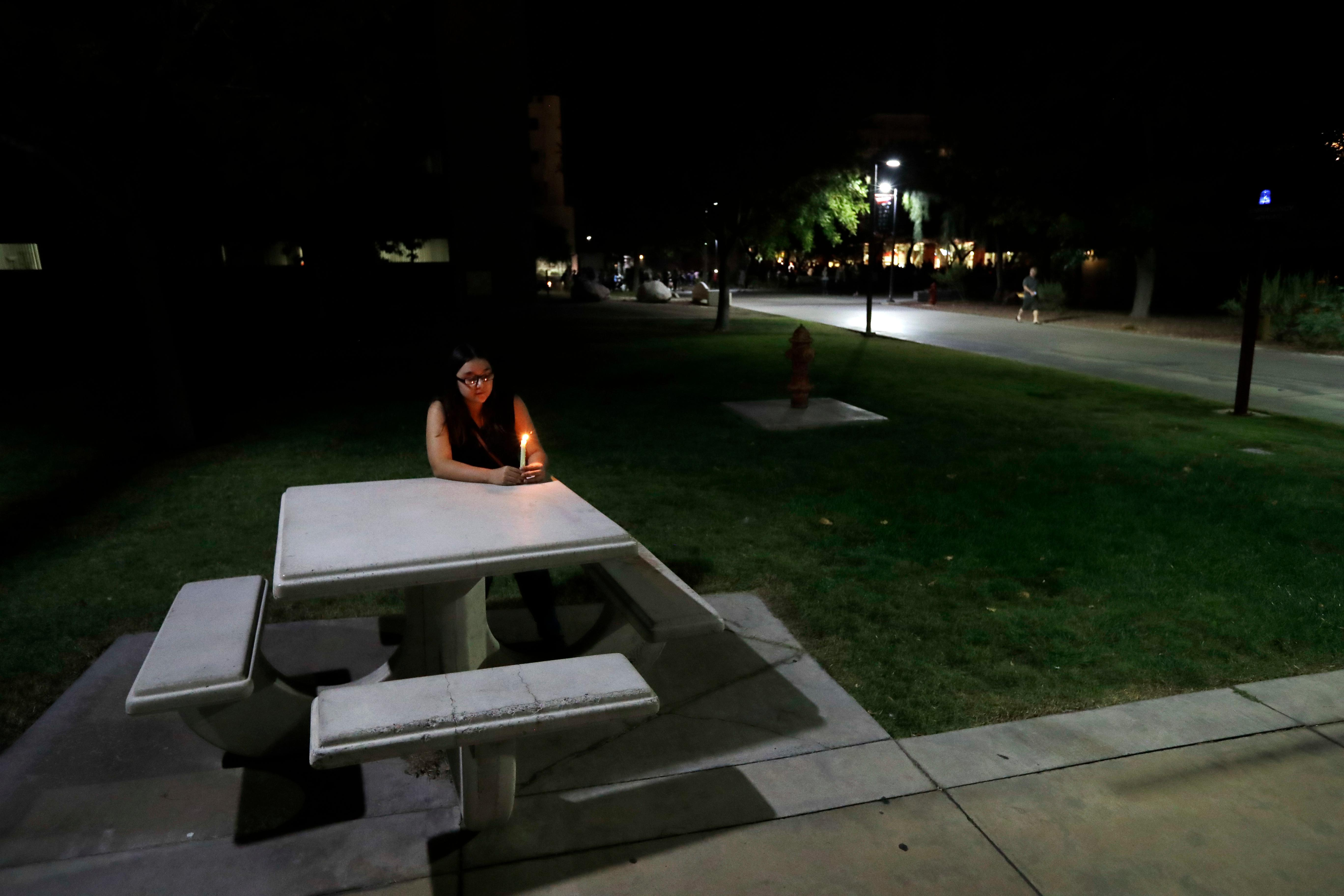 University of Nevada Las Vegas student Johanna Munoz sits at a table with a candle during a vigil Monday, Oct. 2, 2017, in Las Vegas. A gunman on the 32nd floor of the Mandalay Bay casino hotel rained automatic weapons fire down on the crowd of over 22,000 at an outdoor country music festival Sunday. (AP Photo/Gregory Bull)