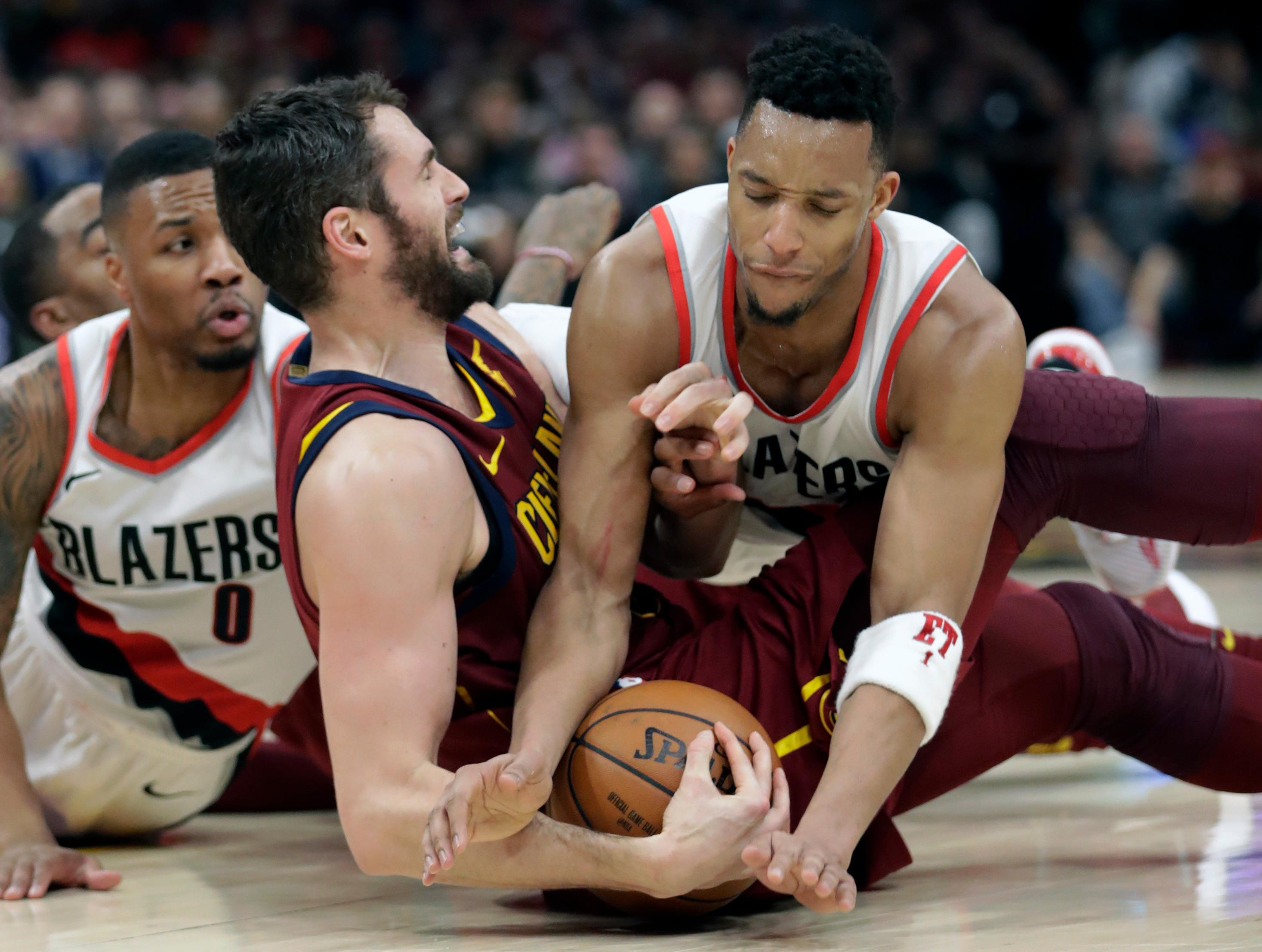 Portland Trail Blazers' Evan Turner, right, tries to get the ball loose from Cleveland Cavaliers' Kevin Love in the first half of an NBA basketball game, Tuesday, Jan. 2, 2018, in Cleveland. (AP Photo/Tony Dejak)
