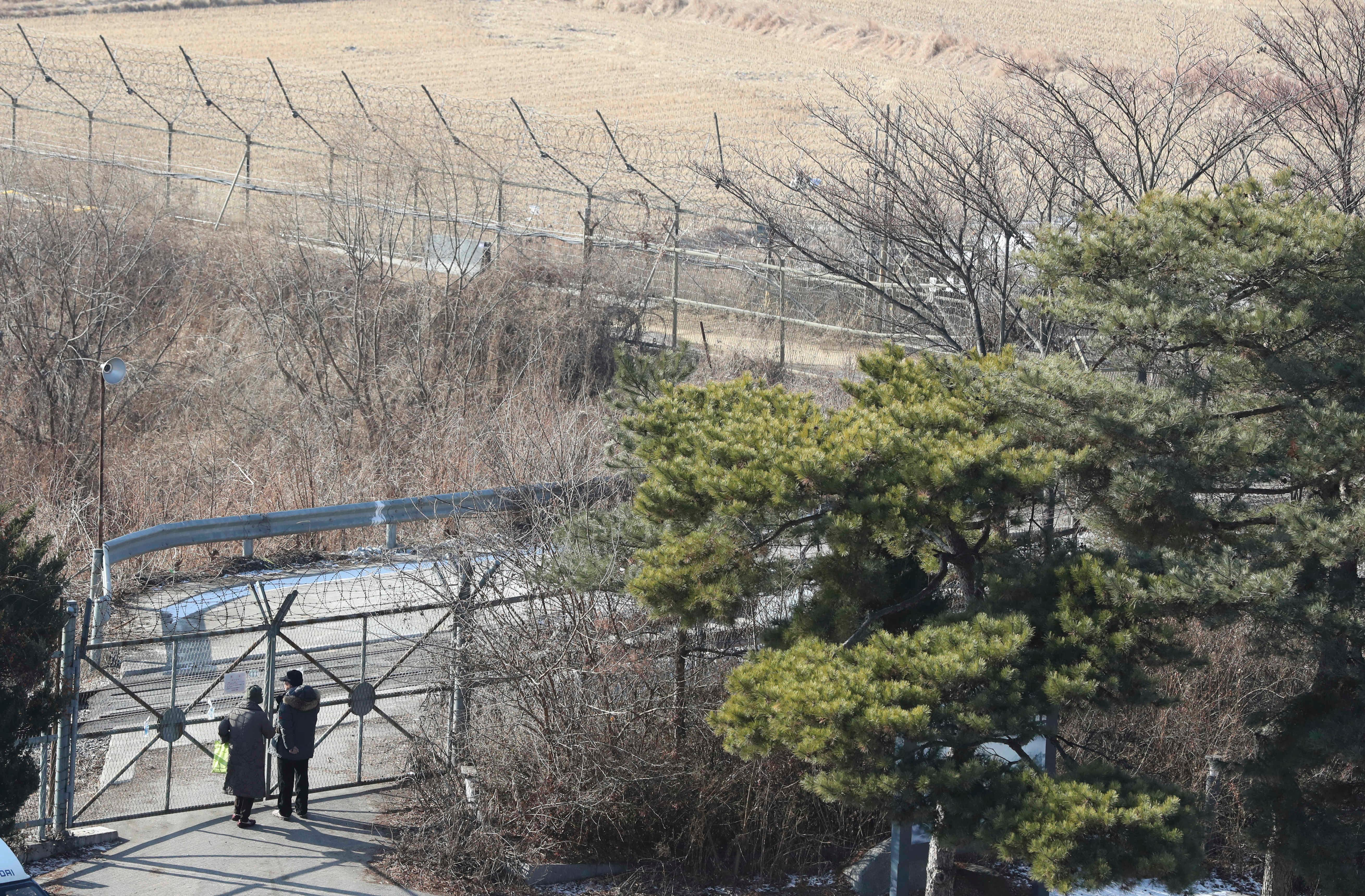 Visitors stand near the military wire fence at the Imjingak Pavilion in Paju, South Korea, Monday, Jan. 1, 2018. North Korean leader Kim Jong Un said Monday the United States should be aware that his country's nuclear forces are now a reality, not a threat. But he also struck a conciliatory tone in his New Year's address, wishing success for the Winter Olympics set to begin in the South in February and suggesting the North may send a delegation to participate. (AP Photo/Lee Jin-man)