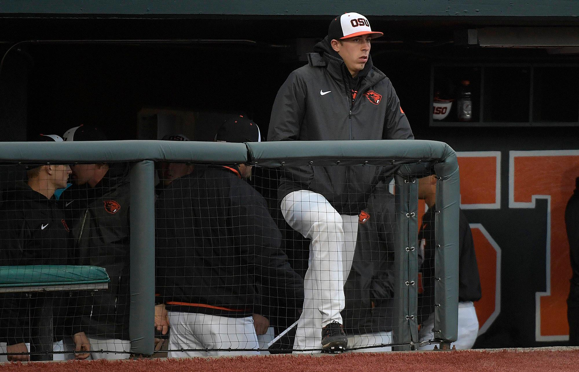 FILE - In this June 9, 2017, file photo, Oregon State's Luke Heimlich watches the team play Vanderbilt during an NCAA college baseball tournament super regional game in Corvallis, Ore. Heimlich, who as a teenager pleaded guilty to molesting a 6-year-old girl, will not accompany the Beavers to the College World Series. The 21-year-old left-hander made the announcement in a statement released through a representative for his family. He called going to the series something that he and his teammates have worked toward all year. (Mark Ylen/Albany Democrat-Herald via AP, file)