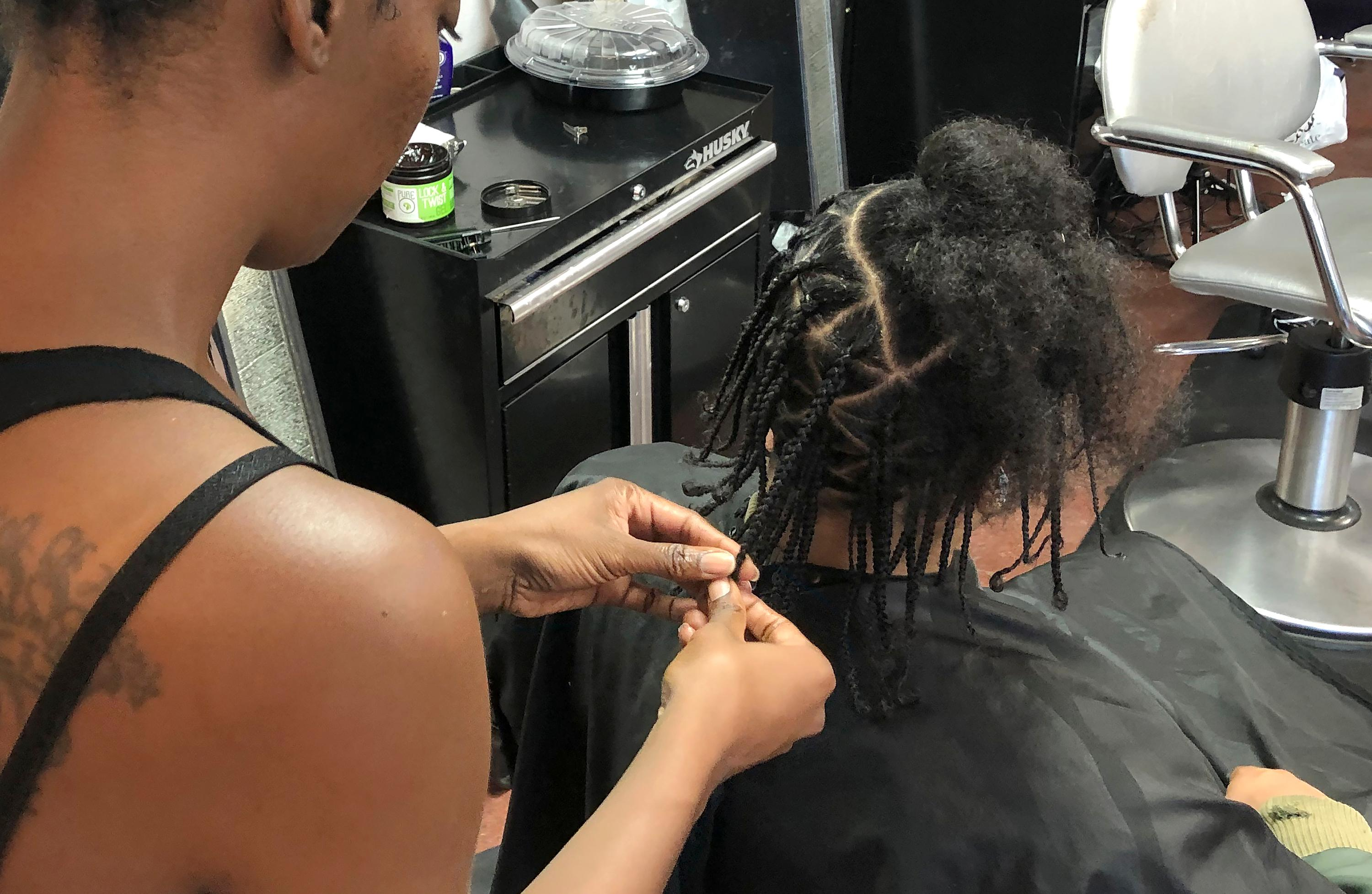 Shana Bonner, left, styles the hair of Pho Gibson at Exquisite U hair salon in Sacramento, Calif., Wednesday, July 3, 2019. Gov. Gavin Newsom signed into law Wednesday a bill making California the first state to ban workplace and school discrimination against black people for wearing hairstyles such as braids, twists and locks. (AP Photo/Kathleen Ronayne)