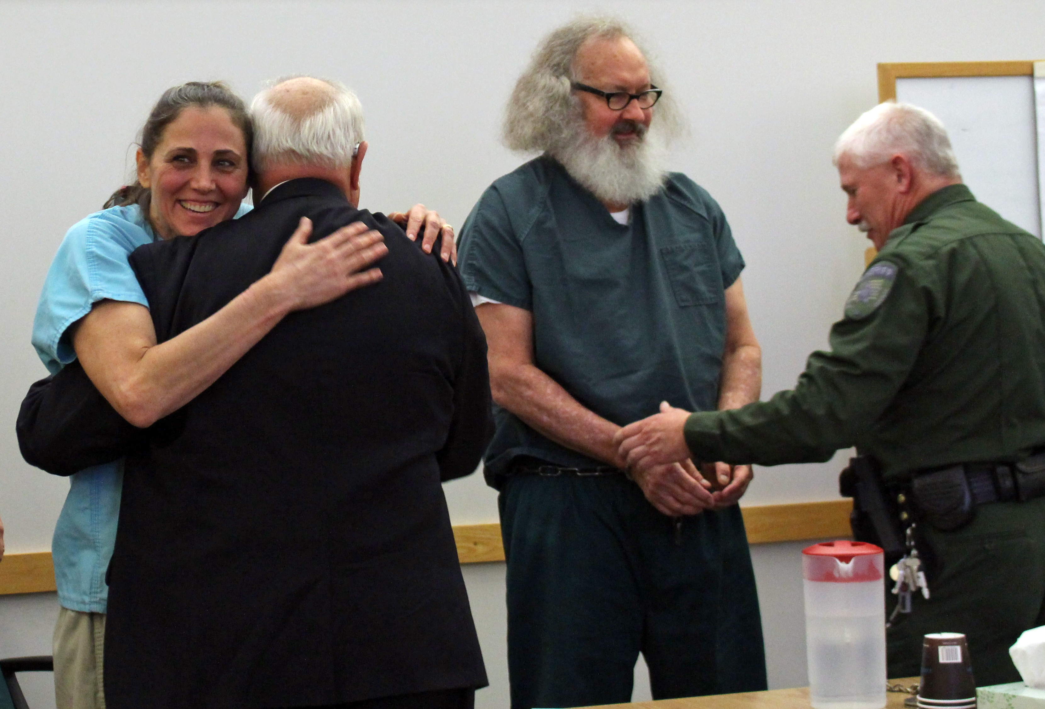 Evi Quaid, left, hugs attorney Peter Langrock and she and her husband, actor Randy Quaid, have their handcuffs removed in court Thursday, Oct. 15, 2015, in St. Albans, Vt. A Vermont judge released the couple, who says they'll now address 5-year-old criminal charges in California.  (Elodie Reed/St. Albans Messenger via AP, Pool)