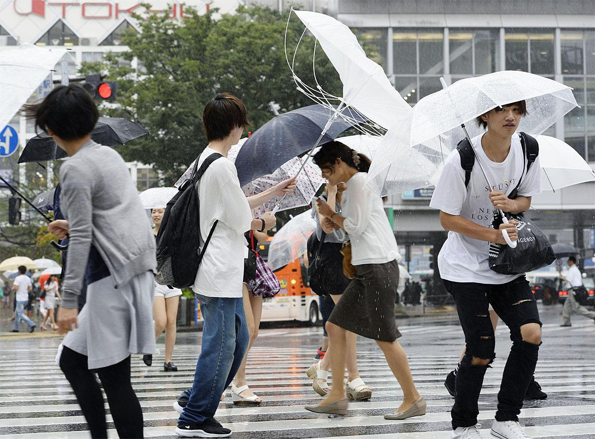 tokyo hot  e754 People walk in a strong wind caused by Typhoon Mindulle, in Tokyo Monday,  Aug