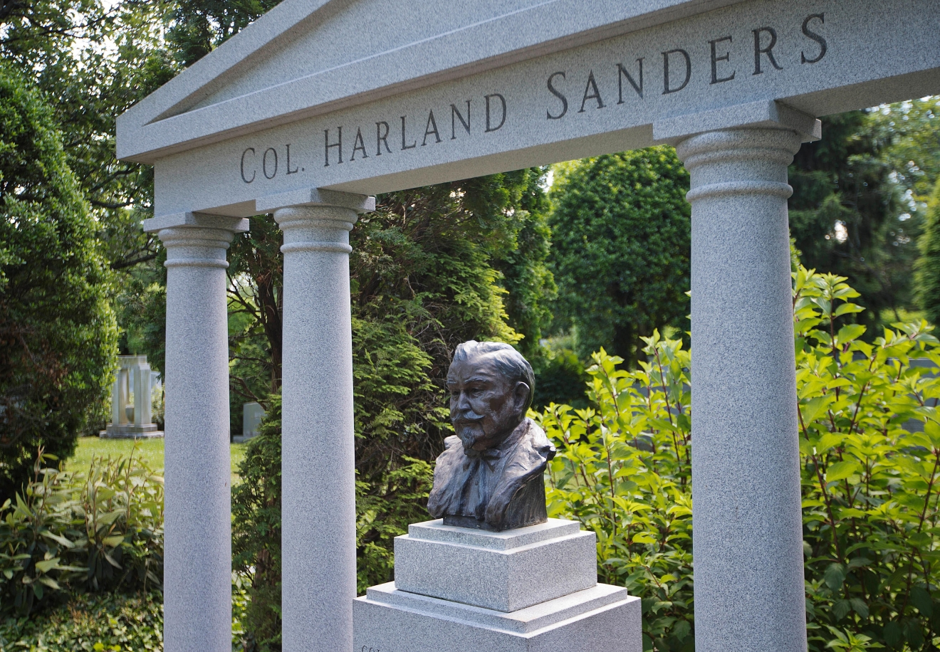 The bust of Colonel Harlan Sanders, the founder of Kentucky Fried Chicken, sits within his granite memorial at Cave Hill Cemetery Tuesday, June 7, 2016, in Louisville, Ky. Muhammad Ali's burial will be in Cave Hill Cemetery, the final resting place for many of the city's most prominent residents. Ali's gravesite will far more subdued, in contrast to his oversized personality and life. A modest marker, in accord with Muslim tradition, is planned, said his attorney, Ron Tweel. (AP Photo/David Goldman)