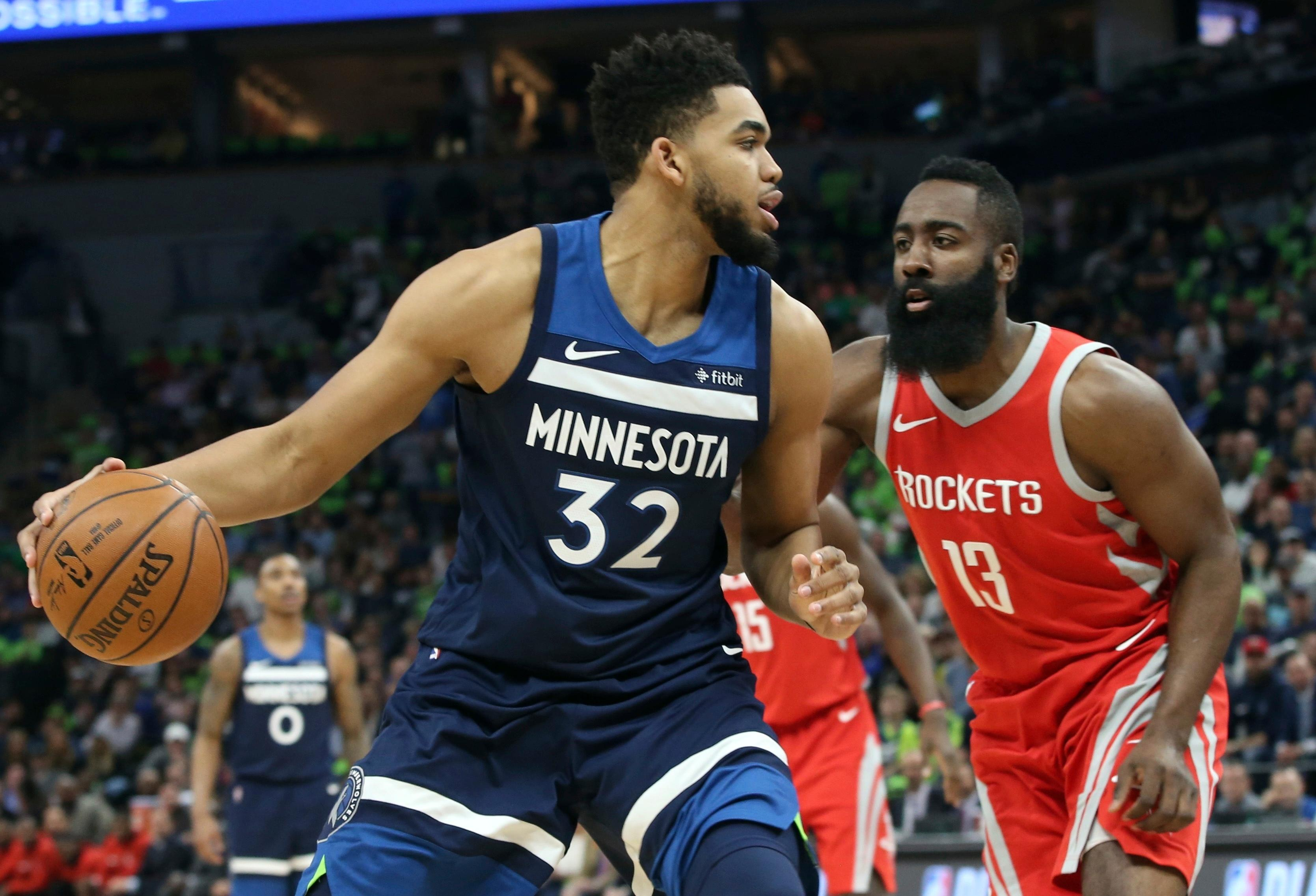 Minnesota Timberwolves' Karl-Anthony Towns, left, works his way around Houston Rockets' James Harden during the first half of Game 4 in an NBA basketball first-round playoff series Monday, April 23, 2018, in Minneapolis. (AP Photo/Jim Mone)