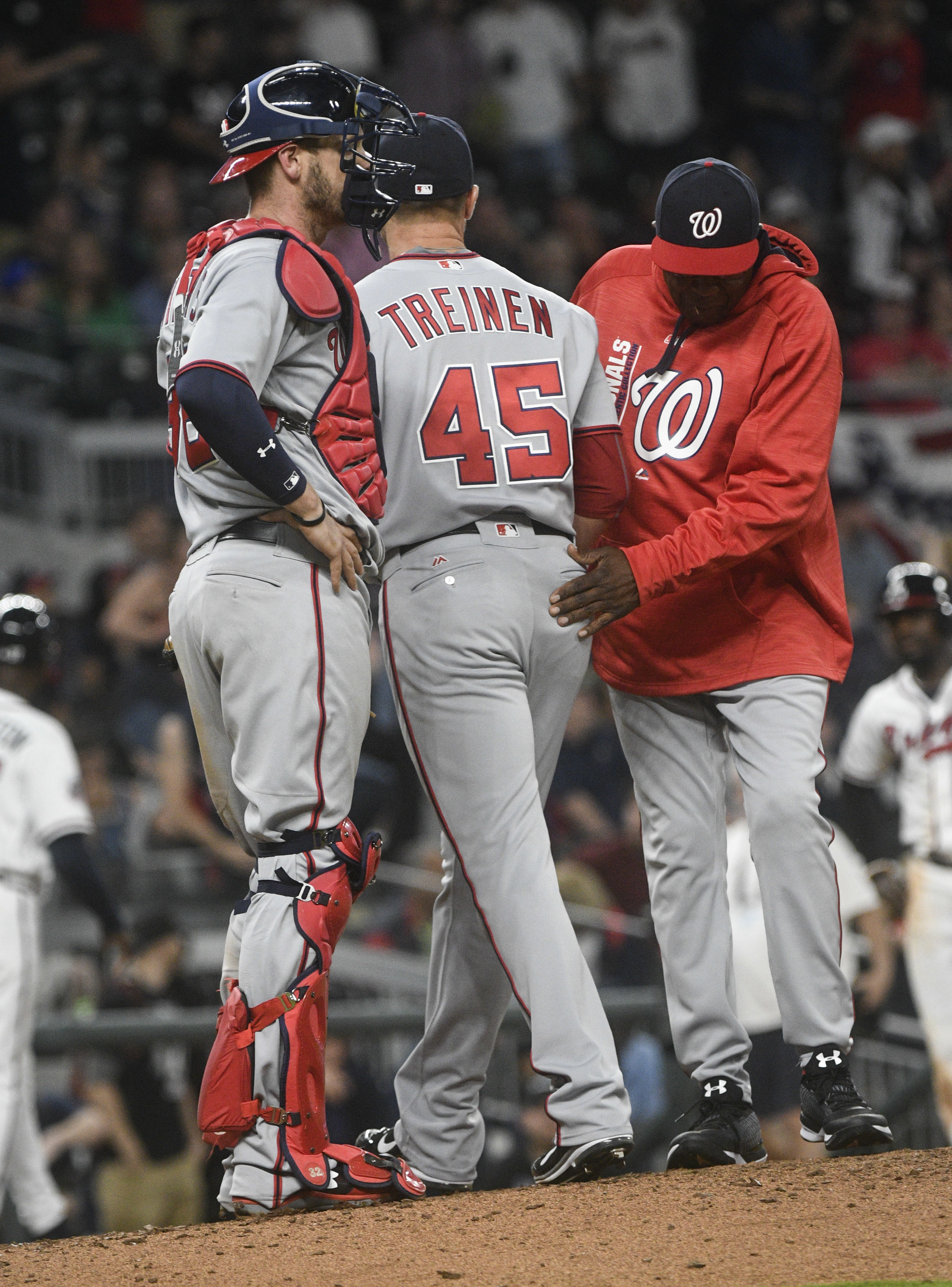 Washington Nationals pitcher Blake Treinen (45) is pulled from the baseball game by manager Dusty Baker, right, as catcher Matt Wieters stands by, after the Atlanta Braves loaded the bases during the ninth inning Tuesday, April 18, 2017, in Atlanta. Washington won 3-1. (AP Photo/John Amis)