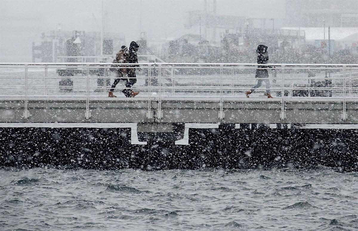People walk over a jetty during heavy snowfall on a jetty in Kiel, northern Germany, Tuesday, Nov. 8, 2016. (Carsten Rehder/dpa via AP)