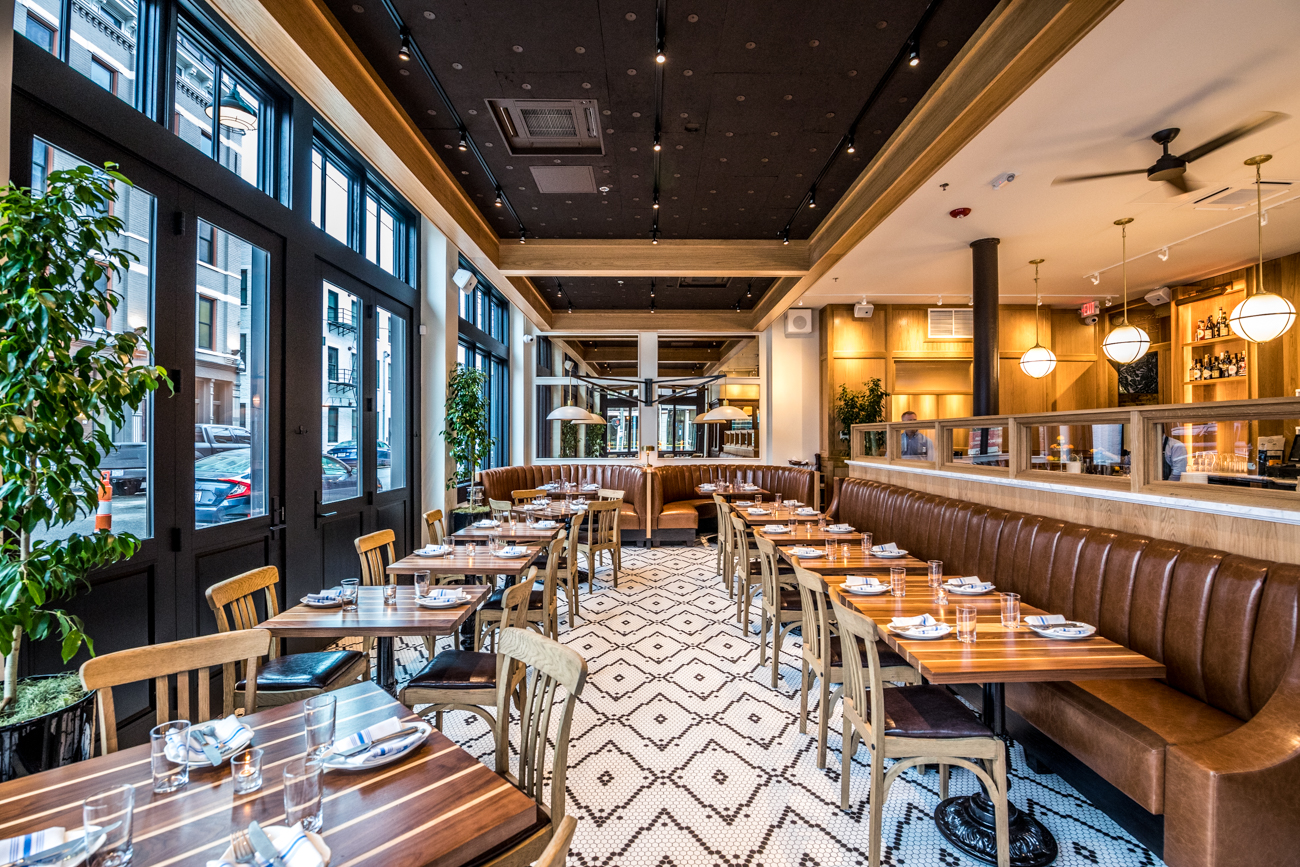 "The main floor of the restaurant is bright with white-tiled flooring, big windows, and marble countertops. By contrast, the basement dining area (accessible by a ""hidden"" double staircase) features a more intimate setting with darker, wooden accents and brass-colored details along with black and white photos covering the walls. / Image: Catherine Viox // Published: 2.11.20"