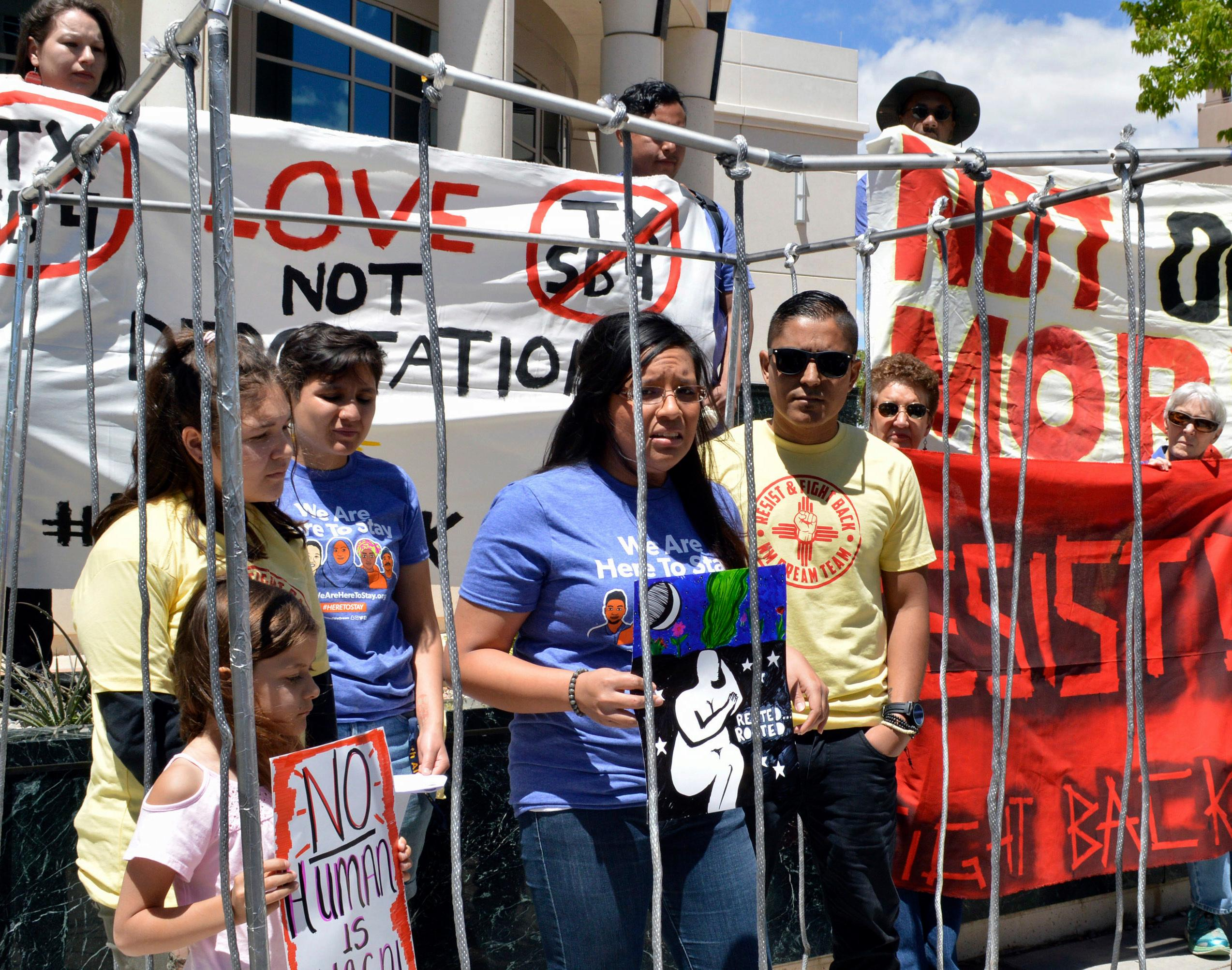 FILE - In this May 1, 2017 file photo, immigrant rights advocates speak out against immigration policies of President Donald Trump while placing themselves in mock detention in Albuquerque, N.M., to mark May Day. The U.S. Justice Department is including New Mexico's most populous county in an effort to pressure cities to cooperate with federal immigration authorities. Bernalillo County was one of roughly two dozen jurisdictions to receive warning letters Wednesday, Jan. 24, 2018, from the Justice Department. (AP Photo/Russell Contreras, File)
