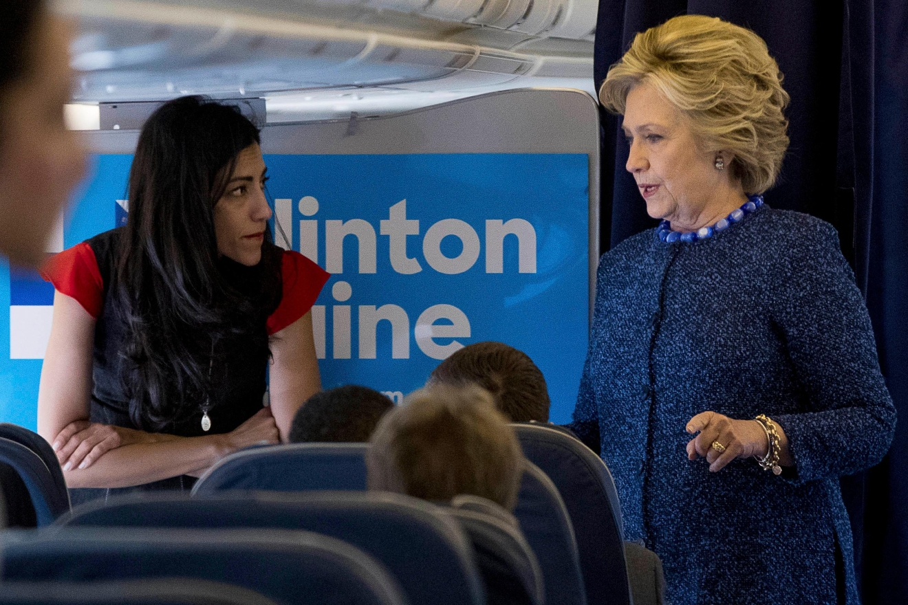FILE - In this Oct. 28, 2016 file photo, Democratic presidential candidate Hillary Clinton speaks with senior aide Huma Abedin aboard her campaign plane at Westchester County Airport in White Plains.  (AP Photo/Andrew Harnik, File)