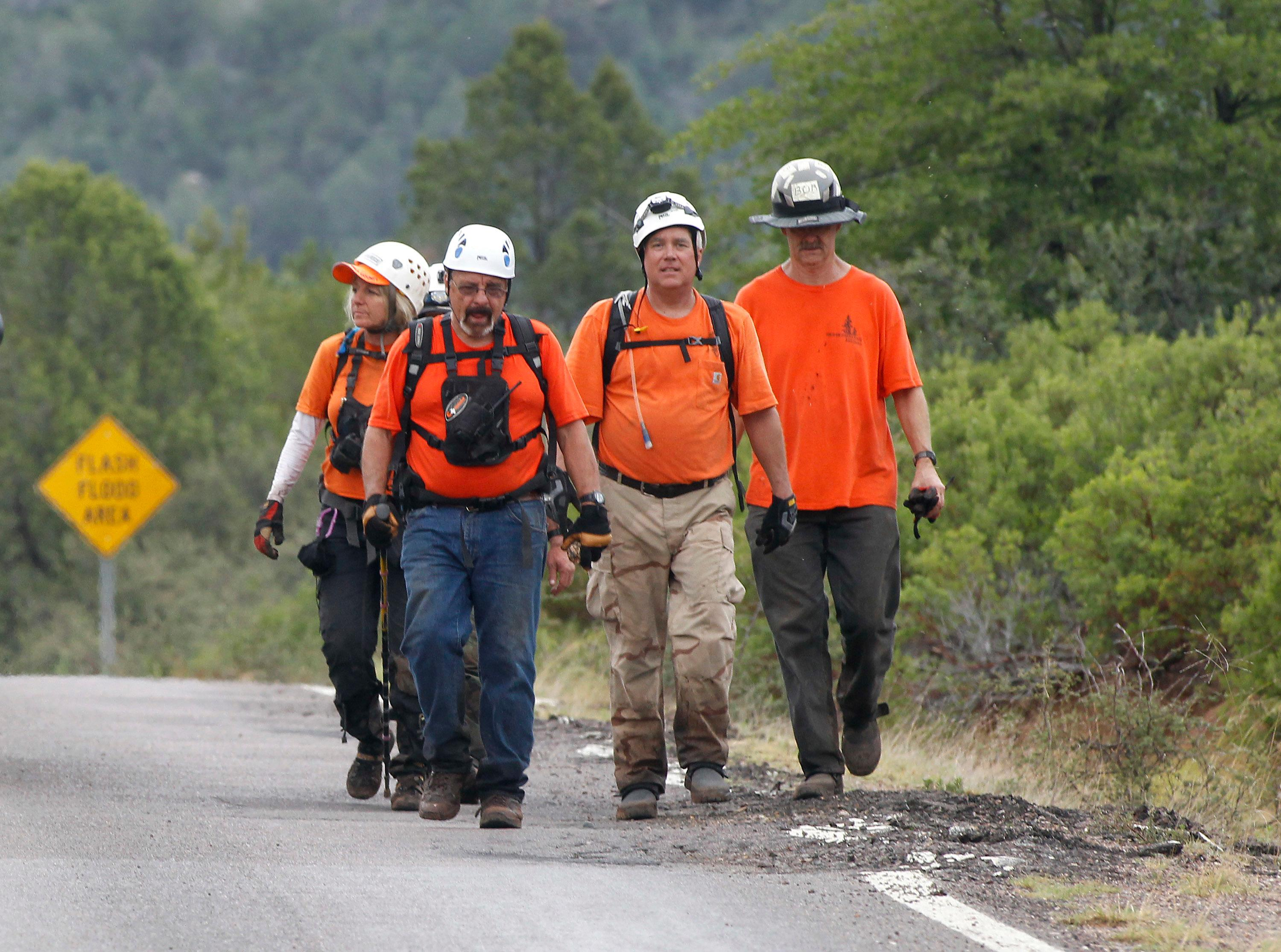 Members of the Tonto Rim Search and Rescue team walk back to the Gila County Sheriff's Office mobile command center after searching along the banks of the East Verde River, Sunday, July 16, 2017, in Payson, Ariz. Search and rescue crews, including 40 people on foot and others in a helicopter, recovered bodies of children and adults, some as far as two miles down the river after Saturday's flash flooding poured over a popular swimming area inside the Tonto National Forest in central Arizona. (AP Photo/Ralph Freso)
