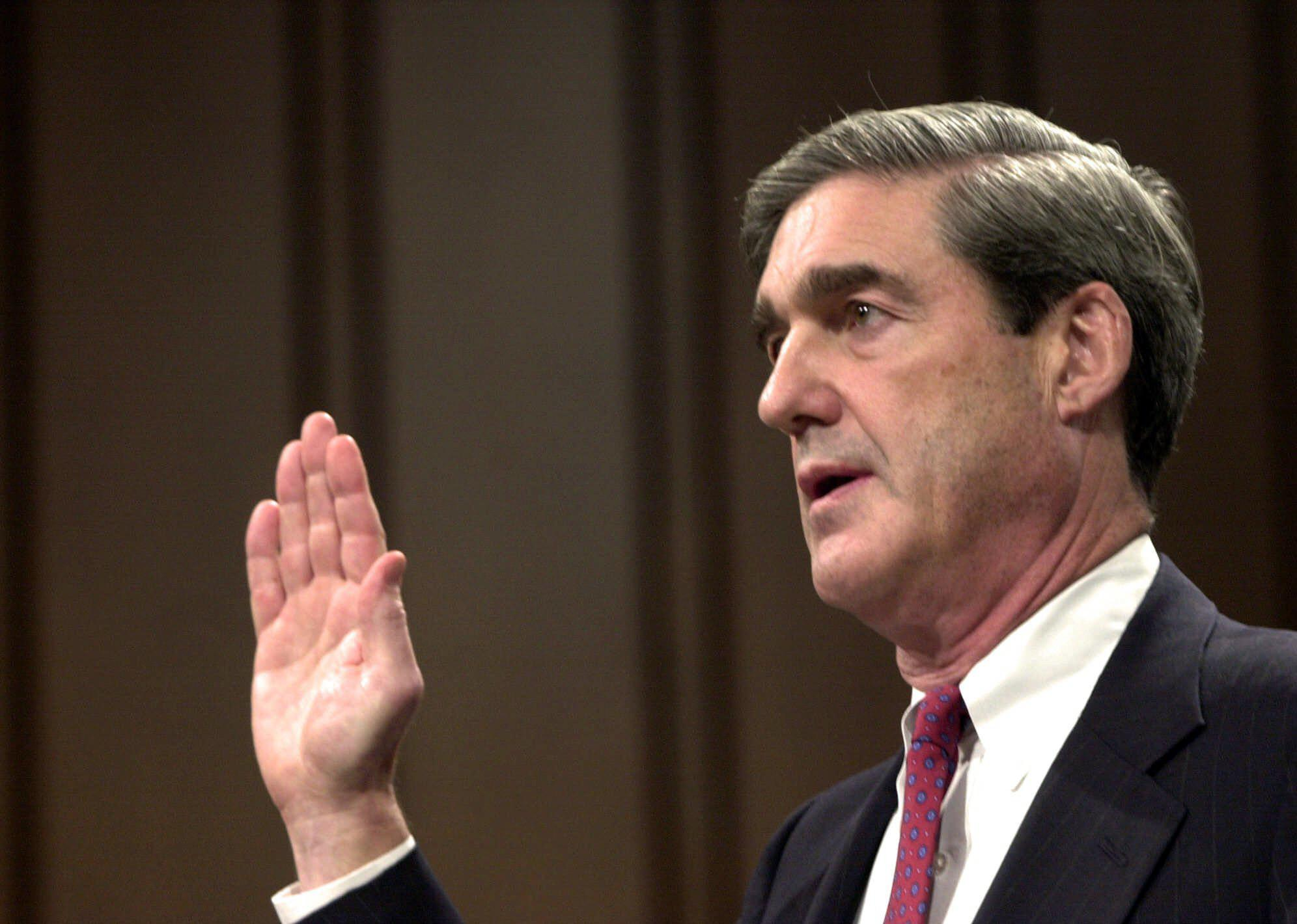 FILE - In this July 30, 2001, file photo, Robert Mueller is sworn in at the start of his testimony during his confirmation hearing before the Senate Judiciary Committee on Capitol Hill in Washington, to be the FBI director. Mueller took office as FBI director in 2001 expecting to dig into drug cases, white-collar misdeeds and violent crime. A week later was Sept. 11. Overnight, his mission changed and Mueller spent the next 12 years wrestling the agency into a battle-hardened terrorism-fighting force. (AP Photo/Dennis Cook, File)