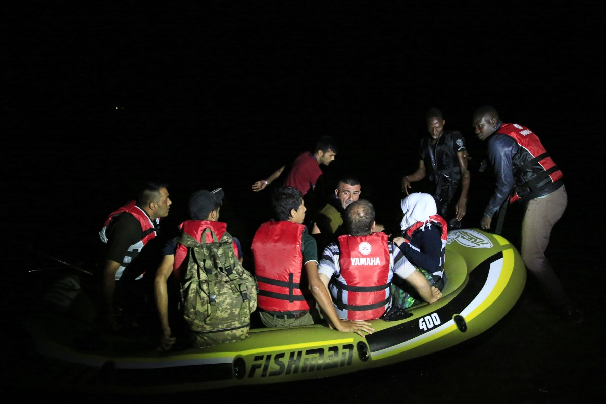 In this early Saturday, Aug. 15, 2015 photo, migrants start their journey on a dinghy from the coastal town of Bodrum, Turkey in order to cross to the nearby Greek island of Kos. The city of Bodrum, a magnet for wealthy tourists, is these days drawing plenty of other visitorsó migrants fleeing conflicts in the Middle East and Africa and seeking a better life in Europe. At its closest point, the Greek island of Kos is only 4 kilometers (2.5 miles) from Turkey and migrants, mostly from Syria, but also from Afghanistan, Iran and African nations often try to cross in groups upward of eight people in small inflatable plastic boats meant for a maximum of four, powered by tiny electric outboard motors and plastic paddles. (AP Photo/Lefteris Pitarakis)