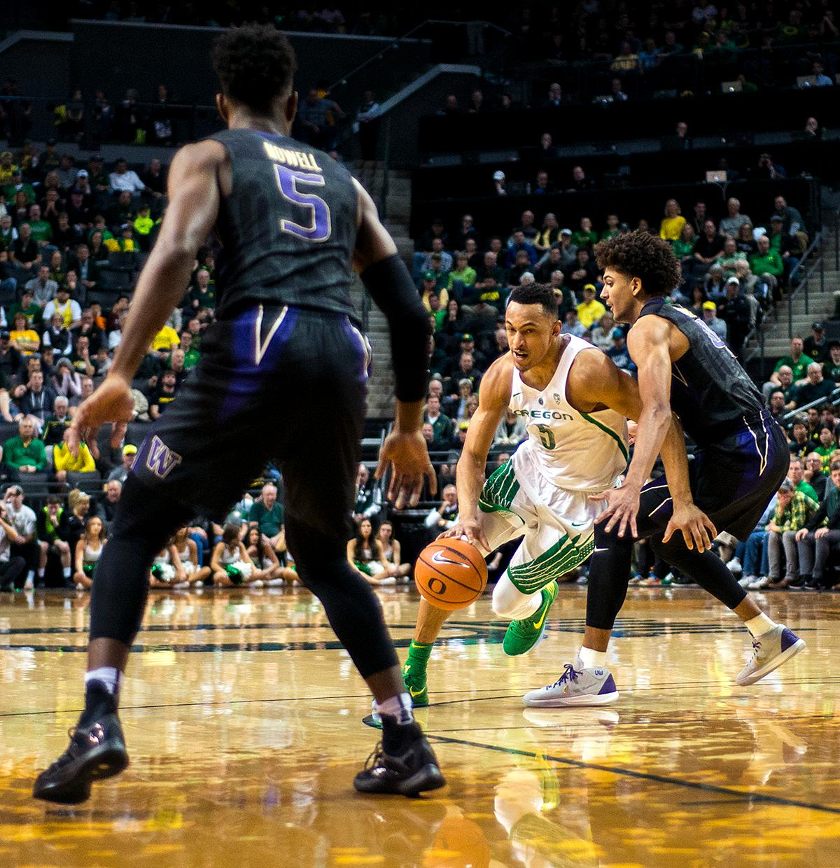 Oregon Ducks guard Elijah Brown (#5) drives hard past Washington Huskies guard Matisse Thybulle (#4). The Oregon Ducks defeated the Washington Huskies 65-40 on Thursday night at Matthew Knight Arena. Troy Brown, Junior led Oregon with 21 points to match his career high, and Kenny Wooten set a career best of seven shots blocked. The Ducks now stand 6-5 in the Pac-12 conference play. Photo by Abigail Winn, Oregon News Lab
