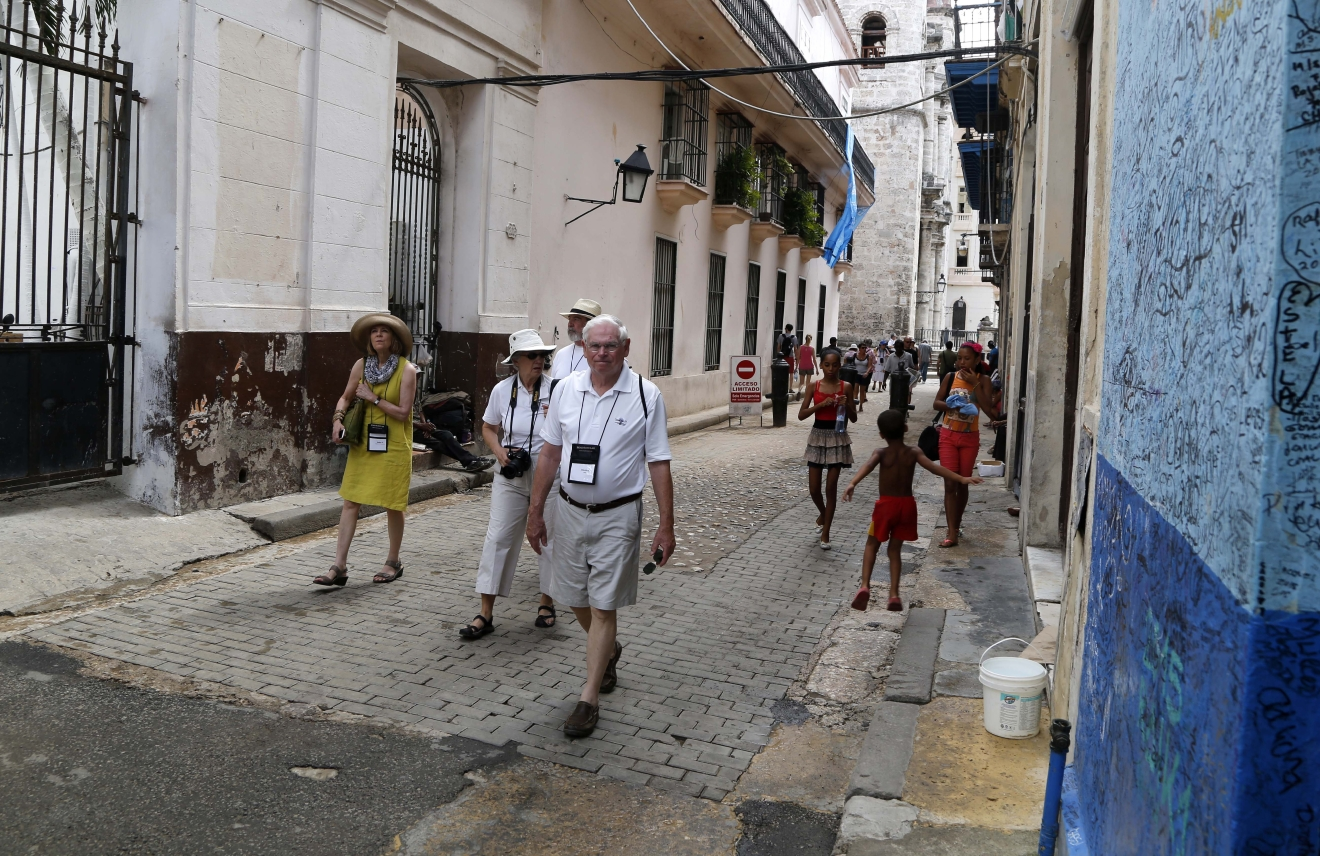 FILE - In this May 24, 2015 file photo, US tourists walks outside the Bodeguita del Medio Bar frequented by the late American novelist Ernest Hemingway in Old Havana, Cuba. One airline's cutback in flights to Cuba may be a sign that demand for travel to the island is slowing down amid uncertainty about Donald Trump's Cuba policies along with a near-doubling of Havana hotel prices and concerns over Zika. (AP Photo/Desmond Boylan, File)