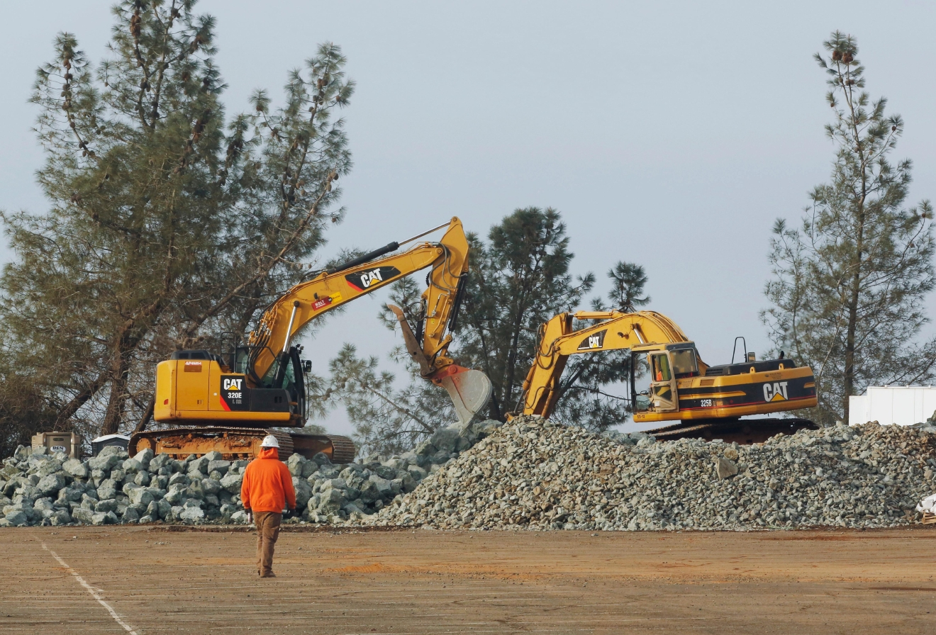 Construction equipment moves piles of rock at a staging area near the Oroville Dam, Monday, Feb. 13, 2017, in Oroville, Calif. State officials have discussed using helicopters to drop loads of rock on the damaged emergency spillway of the dam. (AP Photo/Rich Pedroncelli)