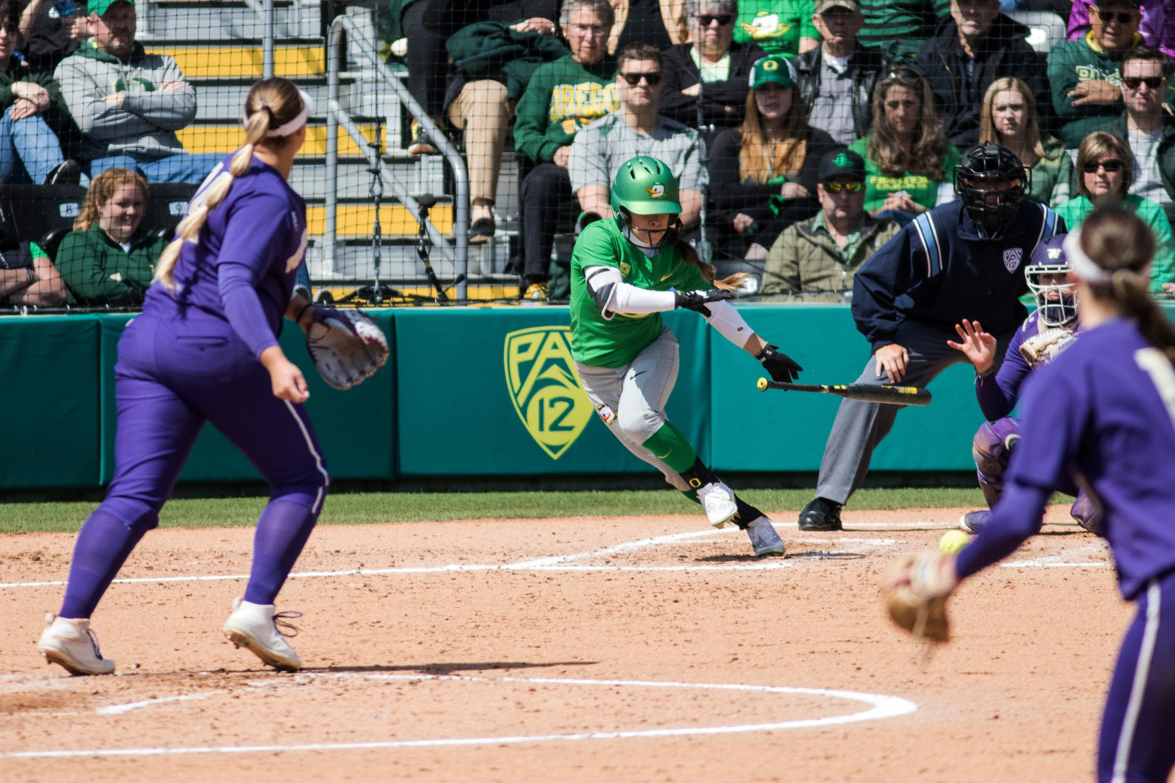 Oregon Ducks infielder Danica Mercado (#2) heads for first base after making contact with the pitch. In the final game of a three-game series, the University of Washington Huskies defeated the Oregon Ducks 5-3.  The Ducks led through the bottom of the 7th inning, but Washington's Morganne Flores (#47) tied it up with a two-run double.  Flores drove in two more runs in the 9th to take the lead.  Photo by Austin Hicks, Oregon News Lab